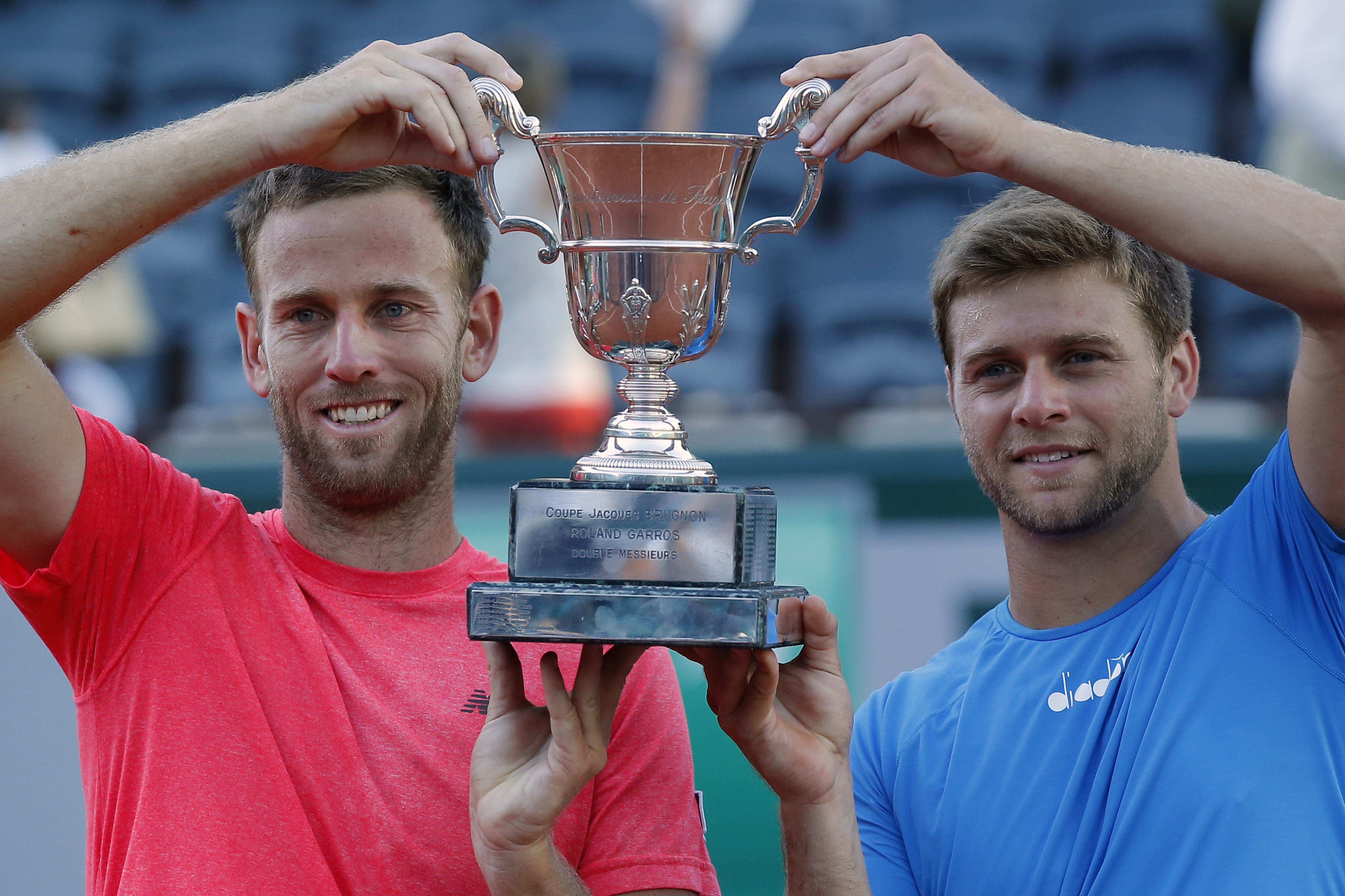 Ryan Harrison of the U.S. and Michael Venus of New Zealand, left, hold the trophy after winning the men's doubles final match of the French Open tennis tournament against Santiago Gonzalez of Mexico and Donald Young of the U.S. in three sets 7-6 (7-5), 6-