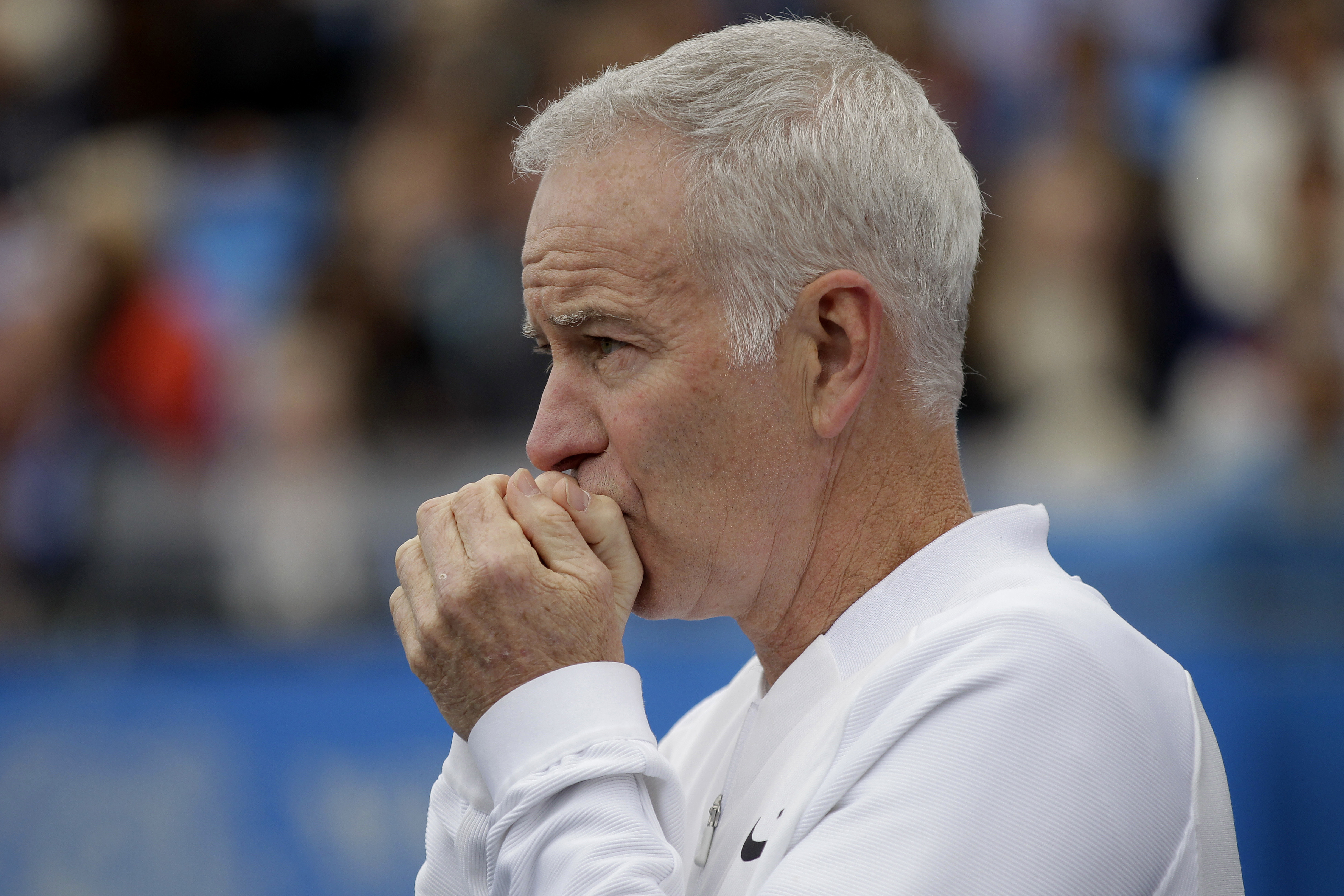 FILE - In a  Saturday June 18, 2016 file photo, John McEnroe, Coach to Canada's Milos Raconic, looks across the court as Raconic plays Australia's Bernard Tomic during their semifinal tennis match on the sixth day of the Queen's Championships London. McEn