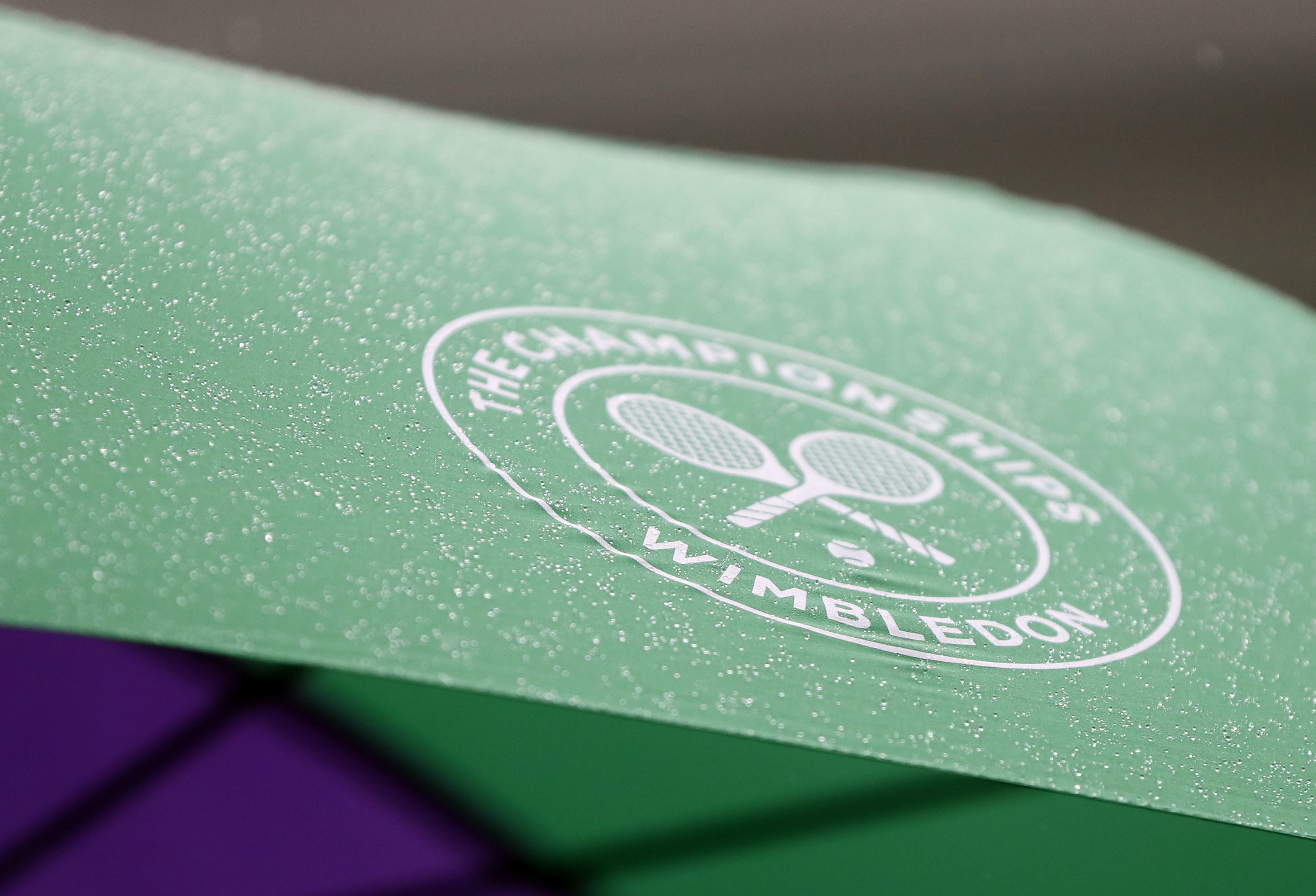 A spectator shelters from the rain on the opening day at the Wimbledon Tennis Championships in London Monday, July 3, 2017. (AP Photo/Kirsty Wigglesworth)