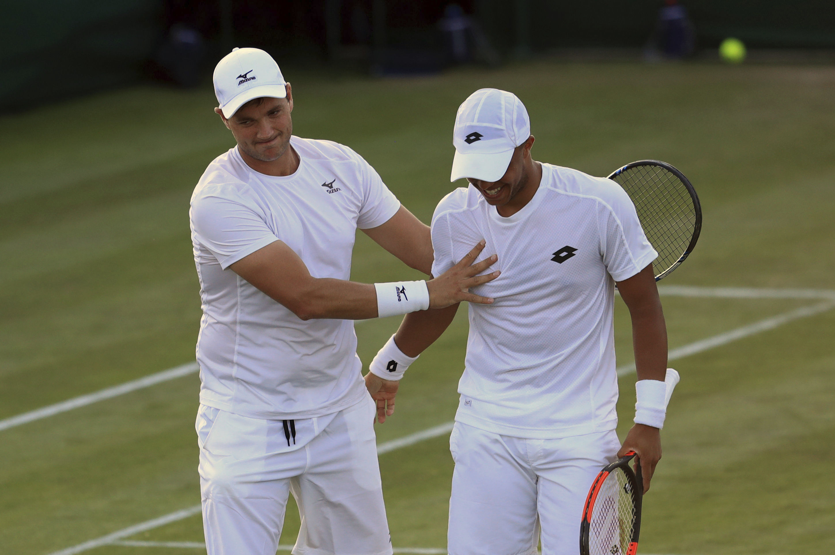 Marcus Willis, left, and Jay Clarke of Britain celebrate winning their doubles match against Jared Donaldson of the US and Jeevan Nedunchezhiyan of India on day three at the Wimbledon Tennis Championships in London, Wednesday, July 5, 2017. (Adam Davy/PA