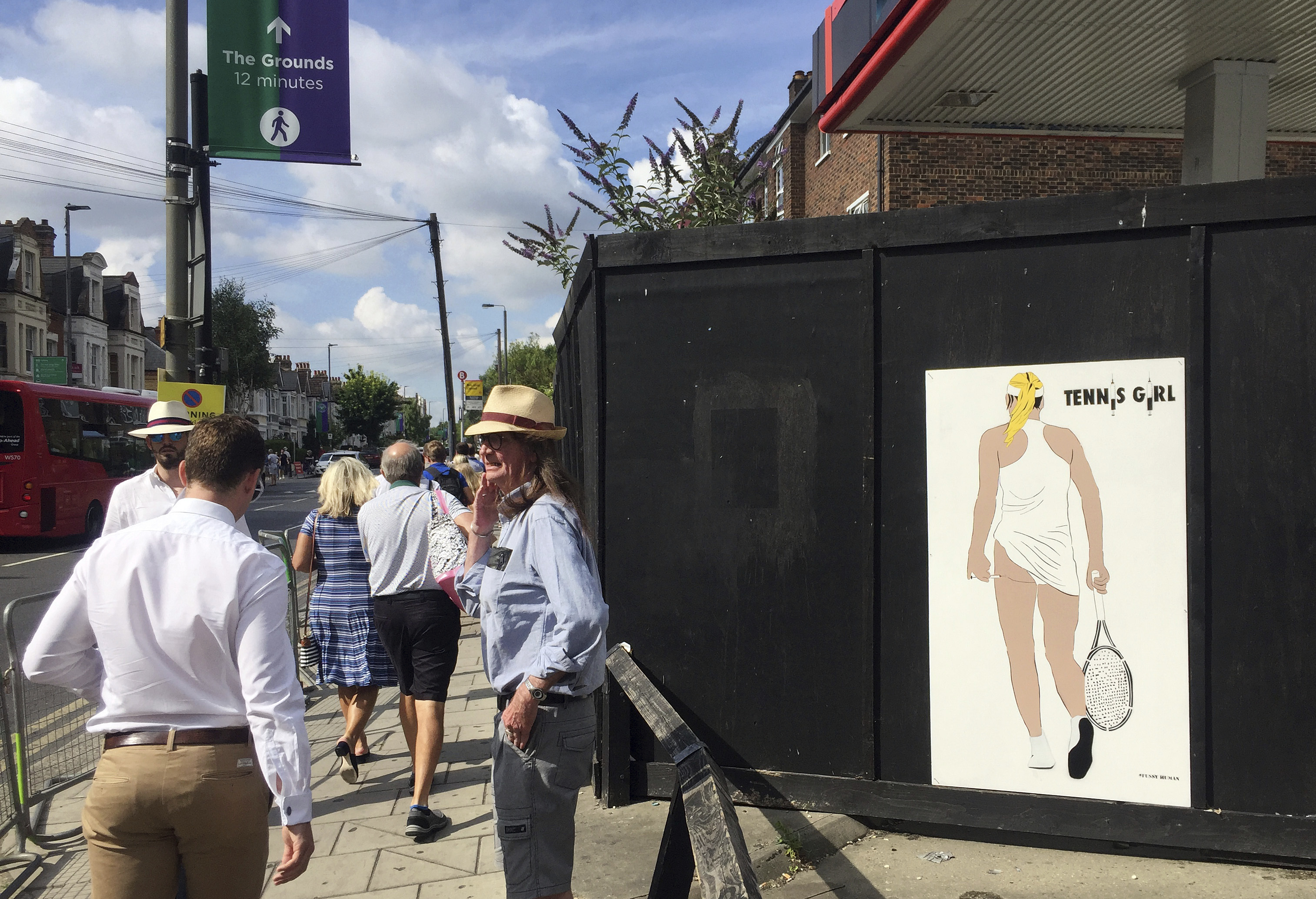 People walk past an artwork by London based street artist 'Fussy Human' near Southfields tube station Monday July 10, 2017. The artwork is a take on a famous poster of the 1970's and was displayed a short walk from the venue of the Wimbledon tennis champi