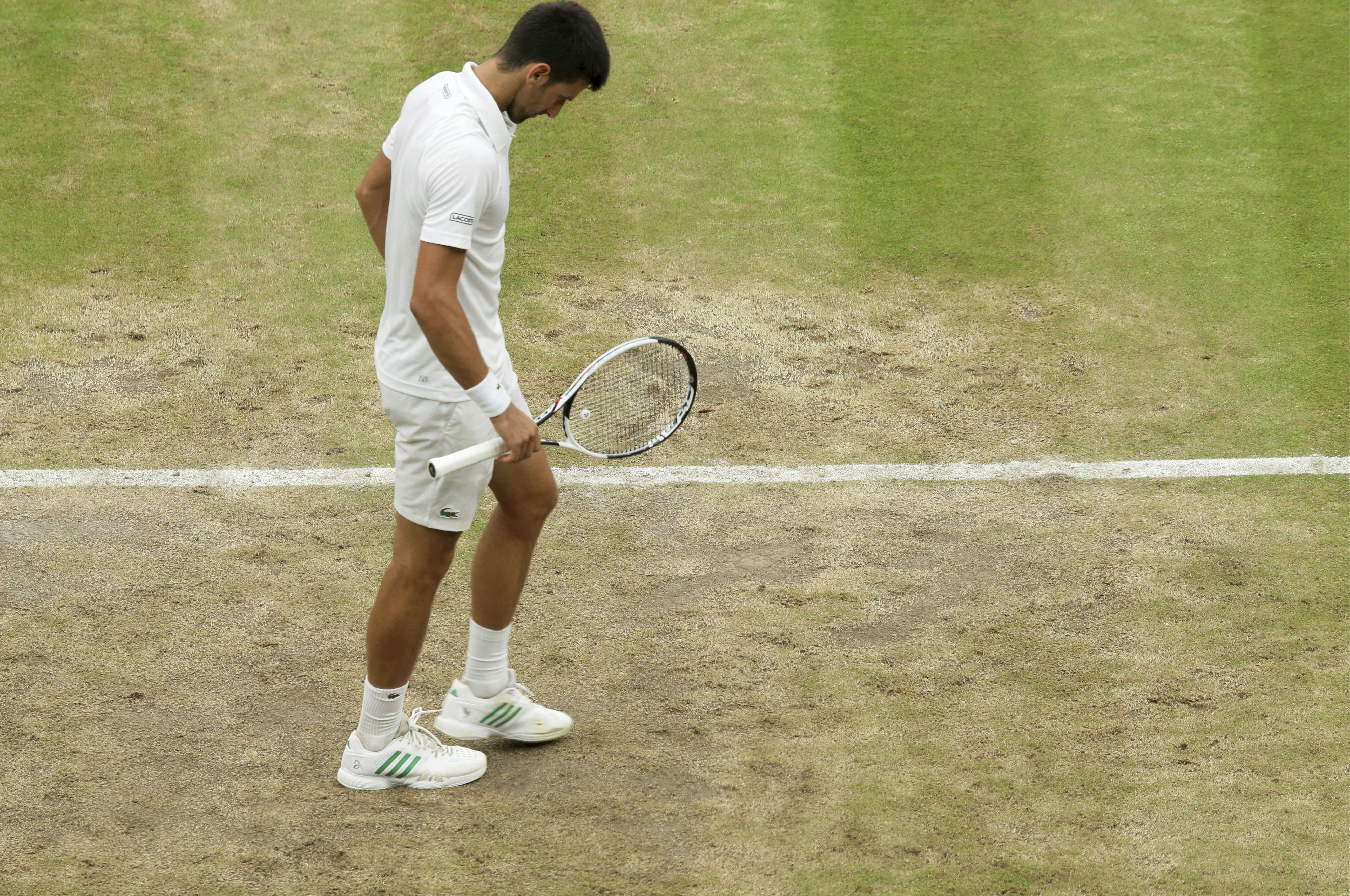 Serbia's Novak Djokovic looks down on the baseline as he plays against Adrian Mannarino of France during their Men's Singles Match on day eight at the Wimbledon Tennis Championships in London Tuesday, July 11, 2017. (AP Photo/Tim Ireland)