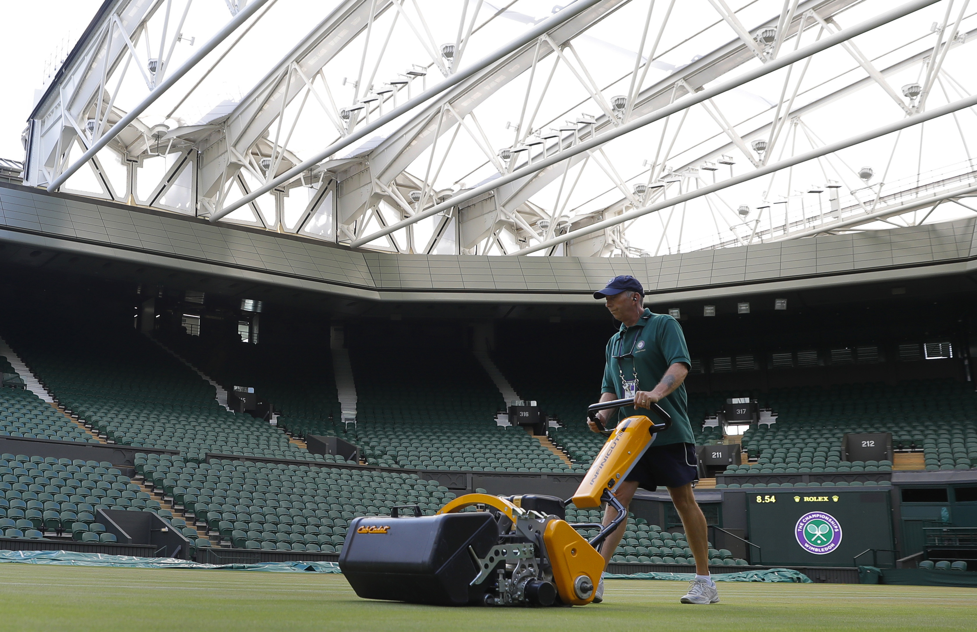 Rick Street mows the grass on Centre Court at the All England Club on day nine at the Wimbledon Tennis Championships in London Thursday, July 13, 2017. At 7:30 a.m. each day of the Wimbledon fortnight, hours before competition begins, the keepers of the g