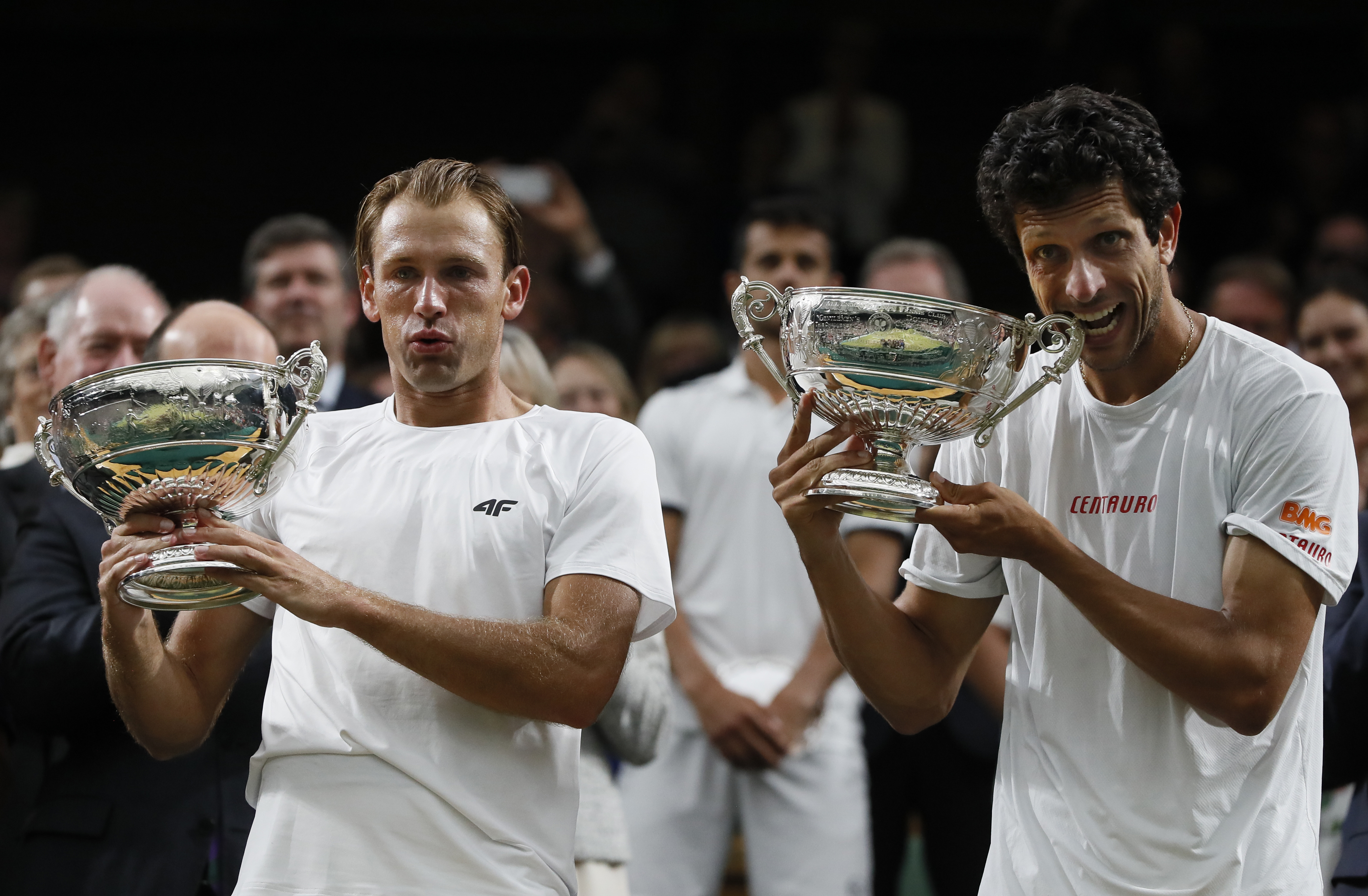 Poland's Lukasz Kubot, left, and Brazil's Marcelo Melo hold up their winners trophies and pose for the media after defeating Austria's Oliver Marach, and Croatia's Mate Pavic in the Men's Doubles final match on day twelve at the Wimbledon Tennis Champions