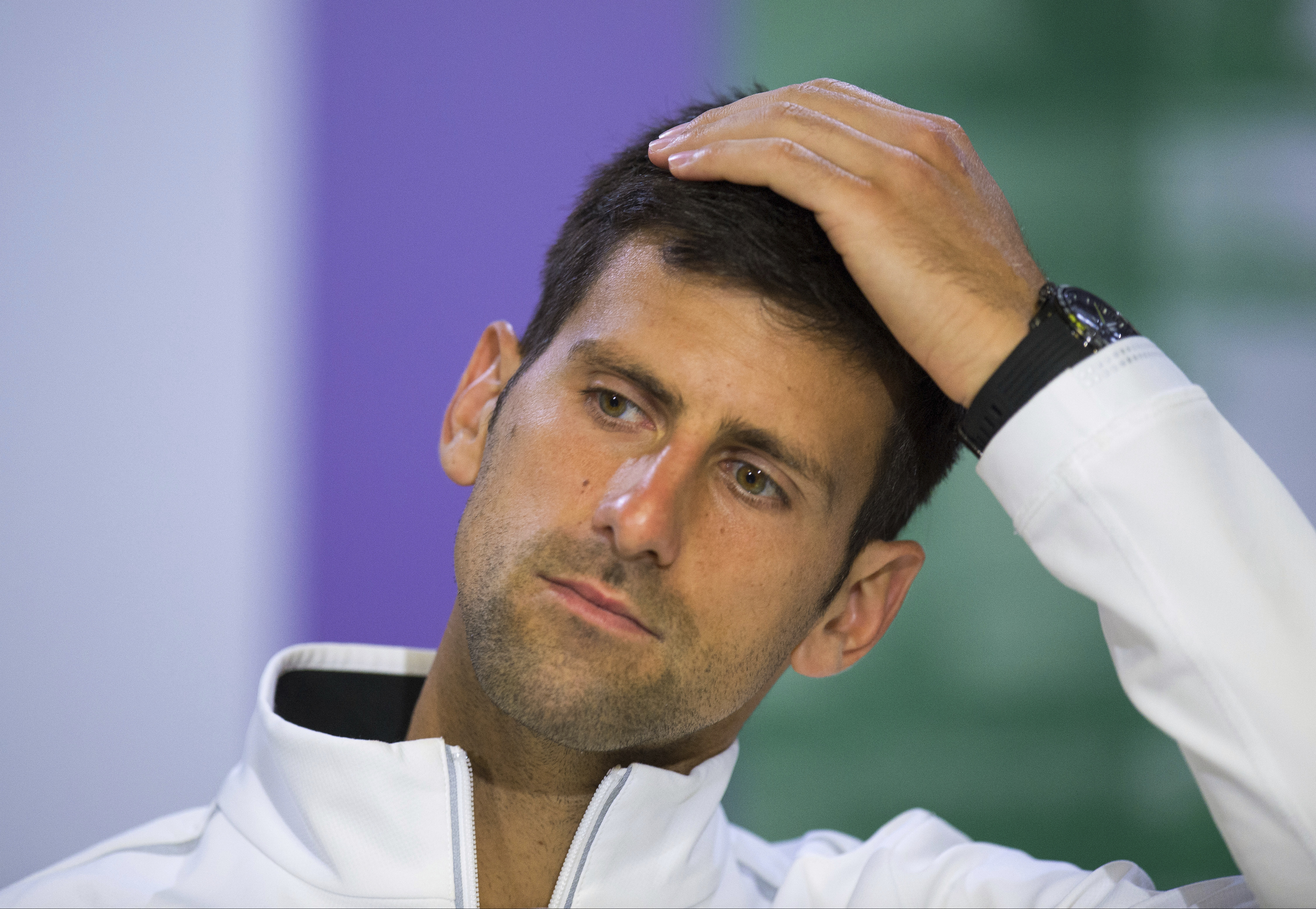 FILE - This is a Wednesday, July 12, 2017 file photo of  Serbia's Novak Djokovic as he gestures during a press conference after losing his Men's Singles Quarterfinal Match against Czech Republic's Tomas Berdych on day nine at the Wimbledon Tennis Champion