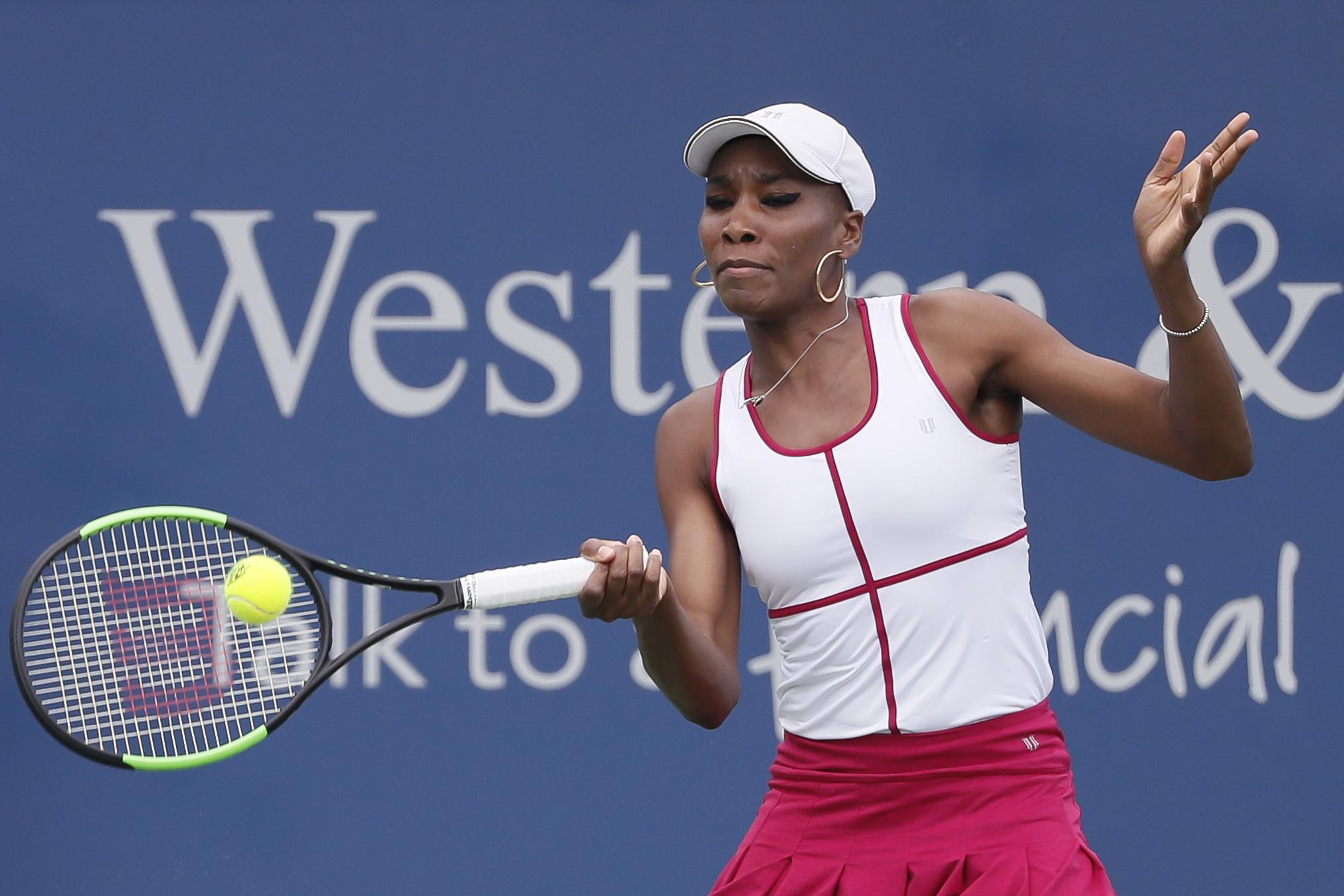 Venus Williams returns to Ashleigh Barty, of Australia, during the middle rounds at the Western & Southern Open tennis tournament, Wednesday, Aug. 16, 2017, in Mason, Ohio. (AP Photo/John Minchillo)