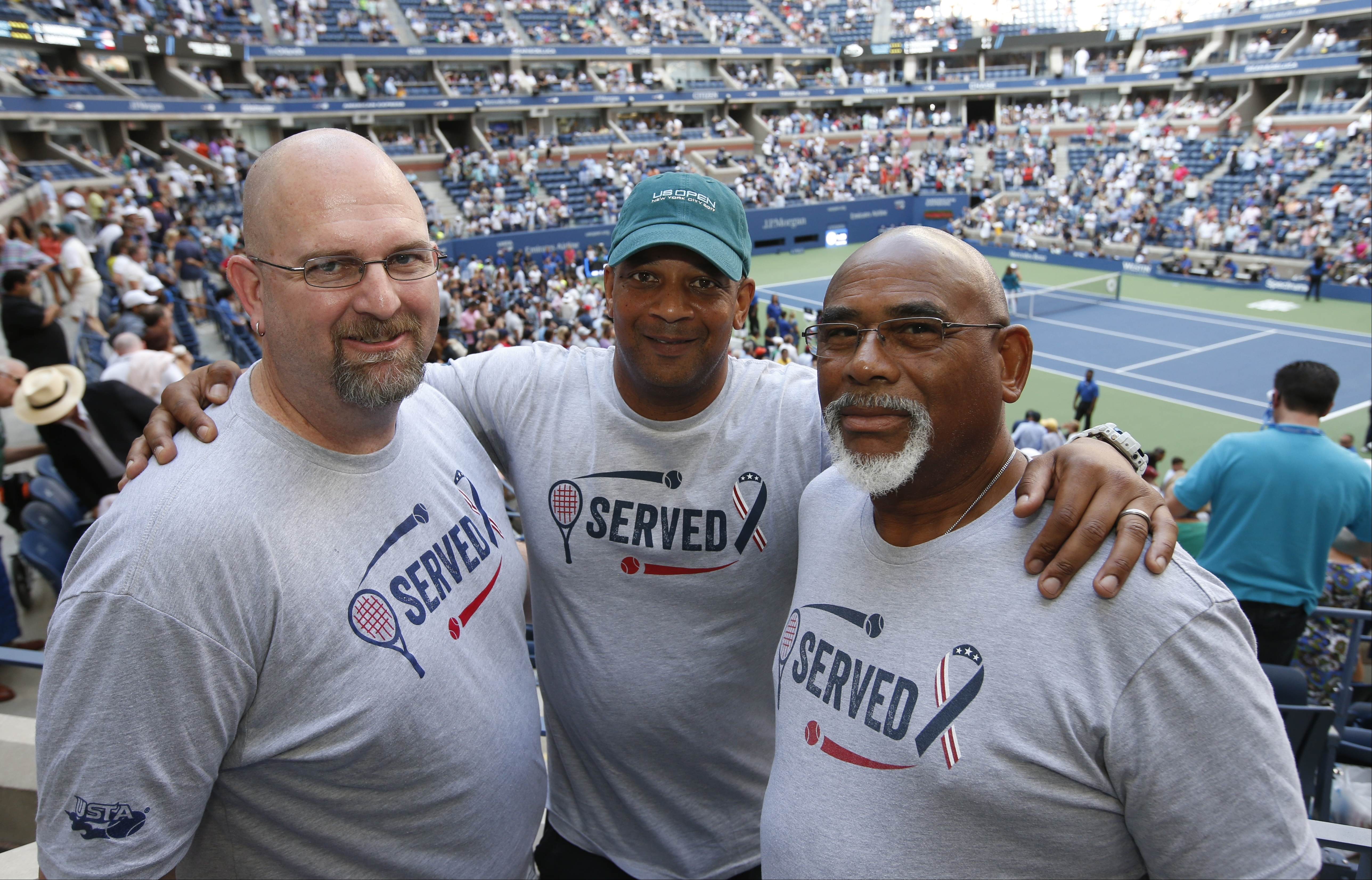 From left, military veterans Marc Spittler, Jon Atkins, and Henry Pruitt, all from Orlando, Fla., pose for a photo during a break in play during the fourth round of the U.S. Open tennis tournament, Monday, Sept. 4, 2017, in New York. (AP Photo/Jason Decro