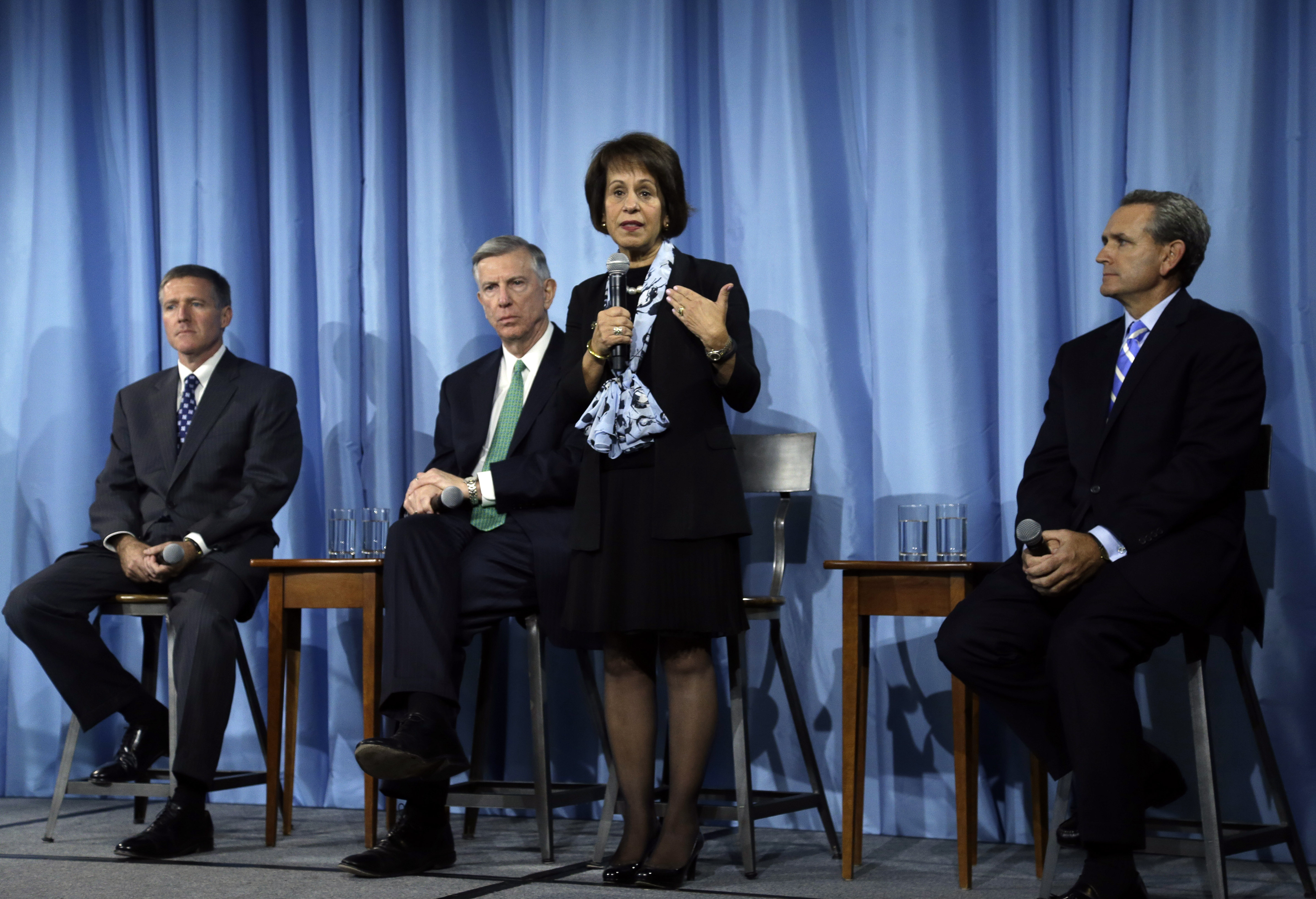 FILE - In this Oct. 22, 2014, file photo, University of North Carolina Chancellor Carol Folt, center, addresses the media following a special joint meeting of the University of North Carolina Board of Governors and the UNC-Chapel Hill Board of Trustees in