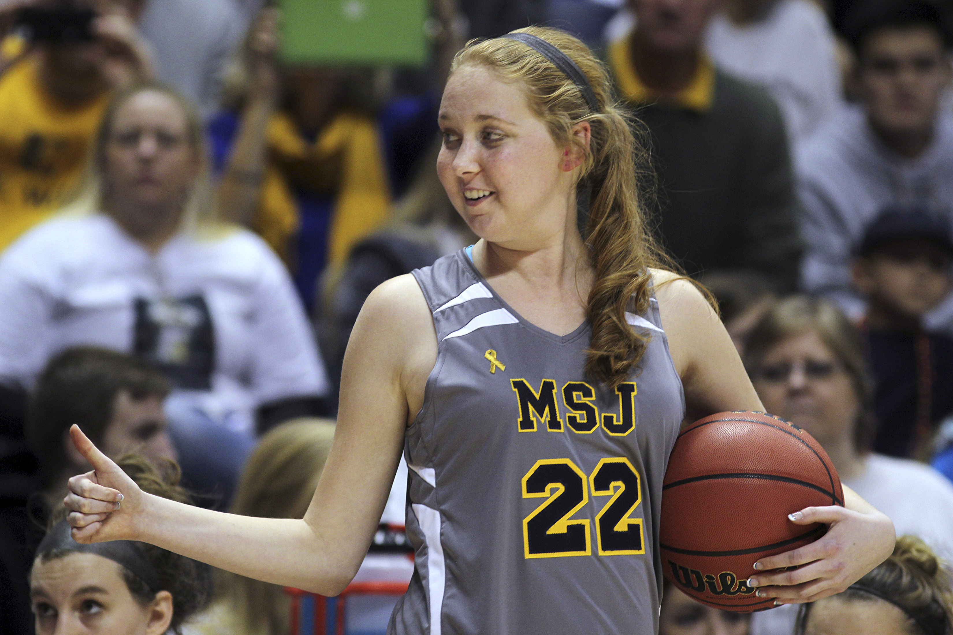 FILE - In this Nov. 2, 2014, file photo, Mount St. Joseph's Lauren Hill gives a thumbs-up as she holds the game ball during her first NCAA college basketball game, against Hiram University, at Xavier University in Cincinnati. Hill will be honored at the E