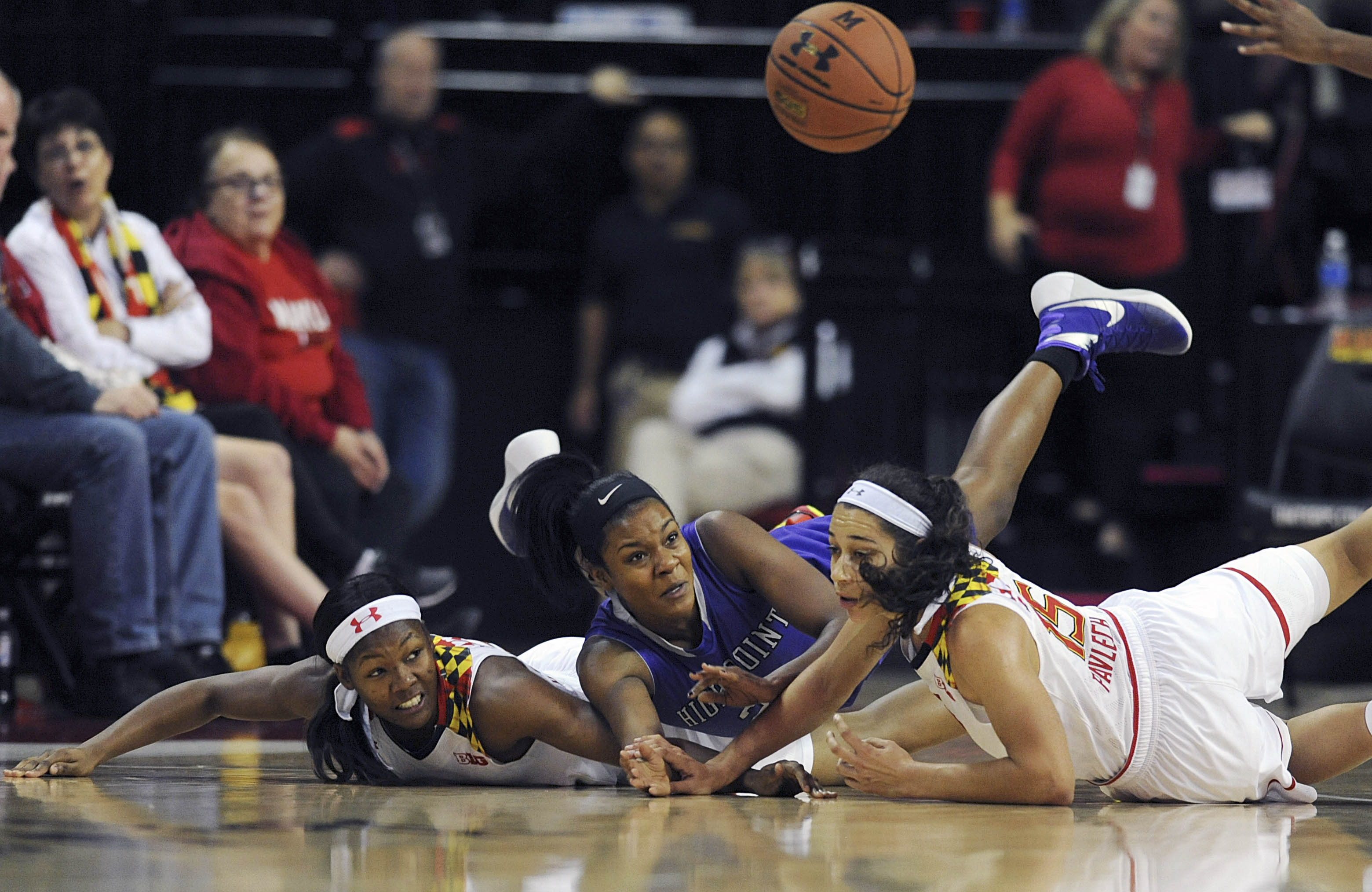 Maryland's A'Lexus Harrison, left, and Chloe Pavlech, right, along with High Point's Lindsey Edwards, center, dive for a loose ball in the first half of an NCAA college basketball game, Wednesday, Nov. 18, 2015 in College Park, Md.(AP Photo/Gail Burton)