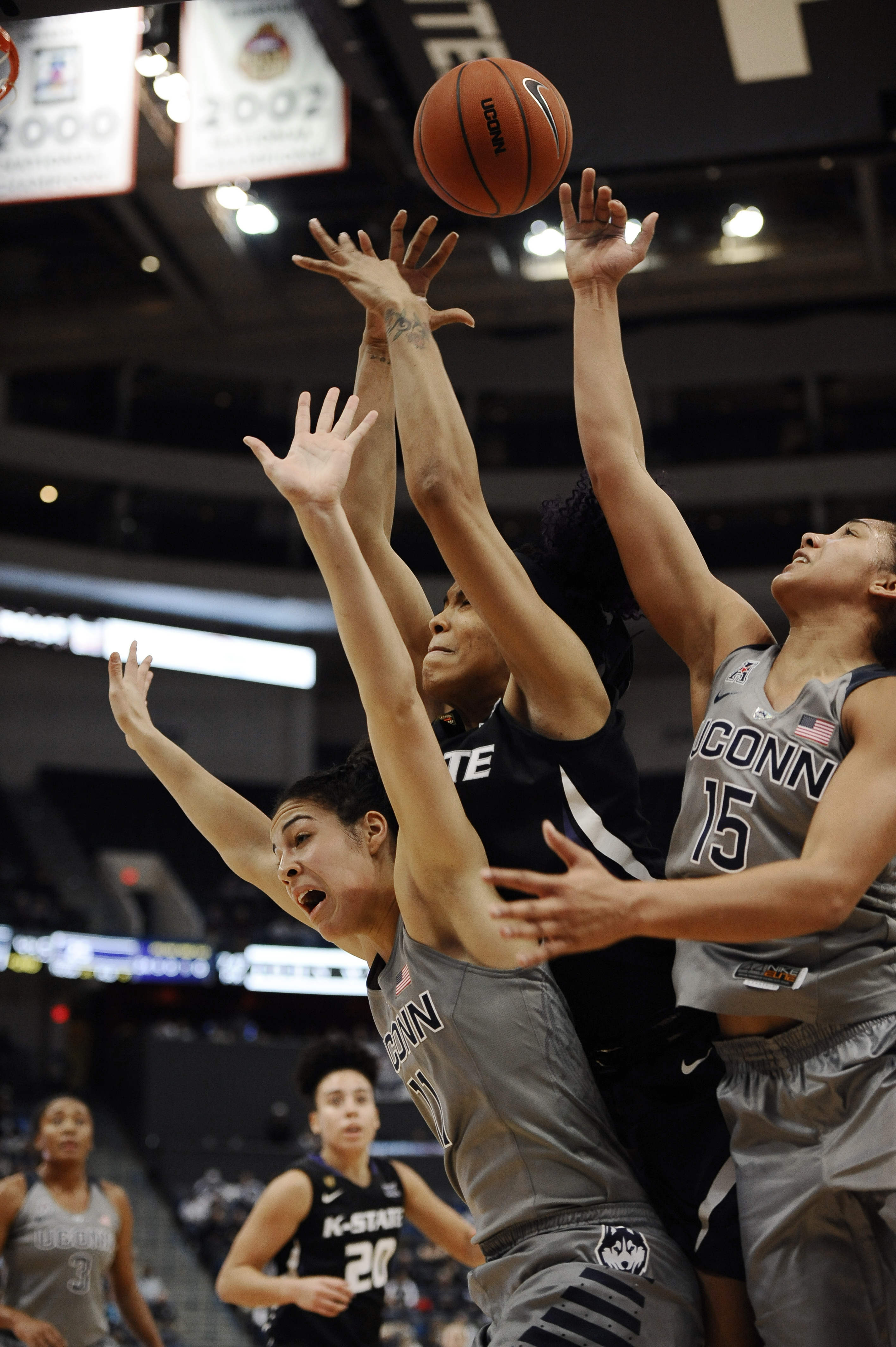 Connecticut's Kia Nurse, left, and Gabby Williams, right, sandwich Kansas State's Erica Young, center, as the vie for a rebound during the first half of an NCAA college basketball game, Monday, Nov. 23, 2015, in Hartford, Conn. (AP Photo/Jessica Hill)