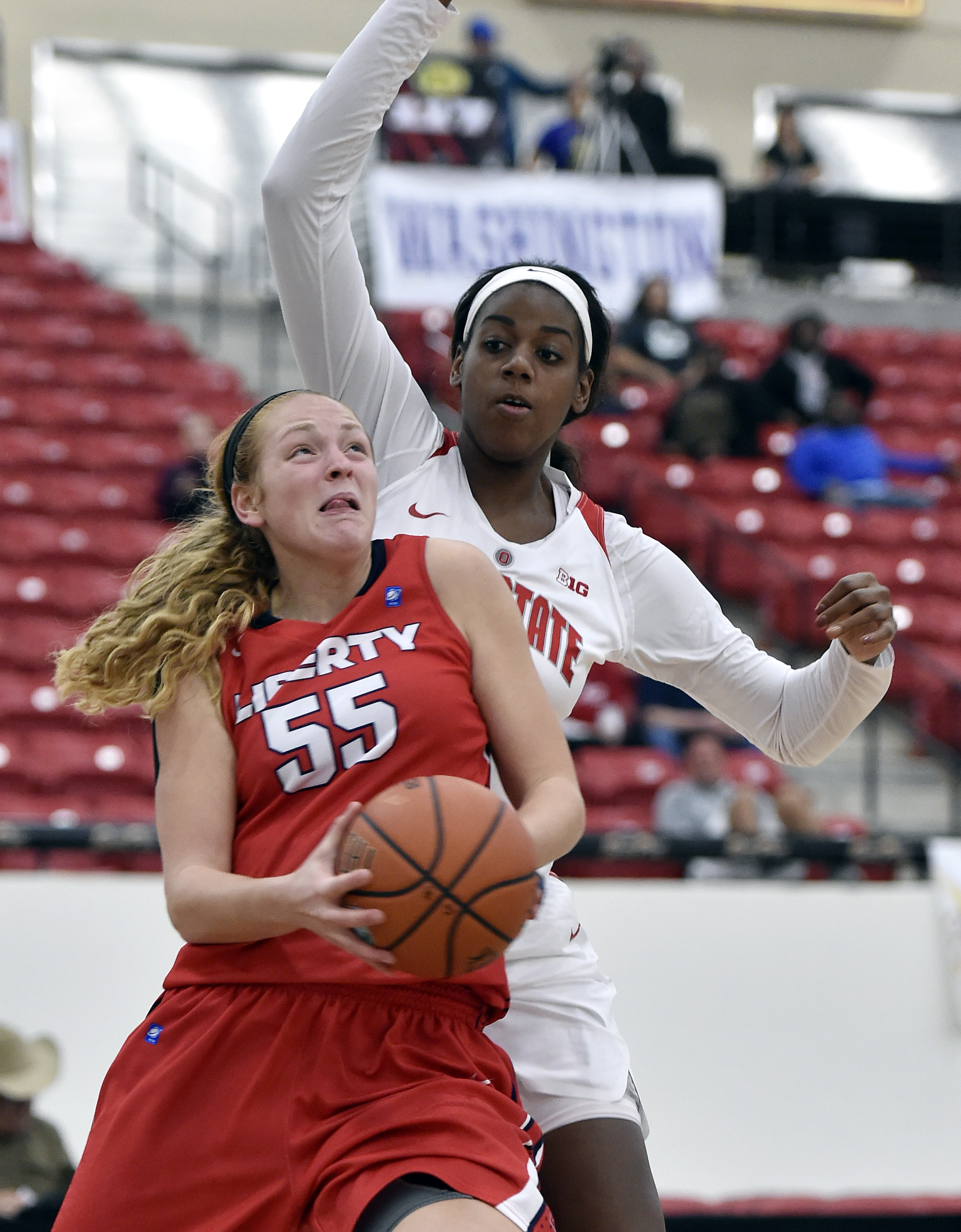 Liberty's Ashley Rininger (55) drives to the basket against Ohio State's Lisa Blair during the second half of an NCAA college basketball game Friday, Nov. 27, 2015, in Las Vegas. Ohio State won 75-65. (AP Photo/David Becker)