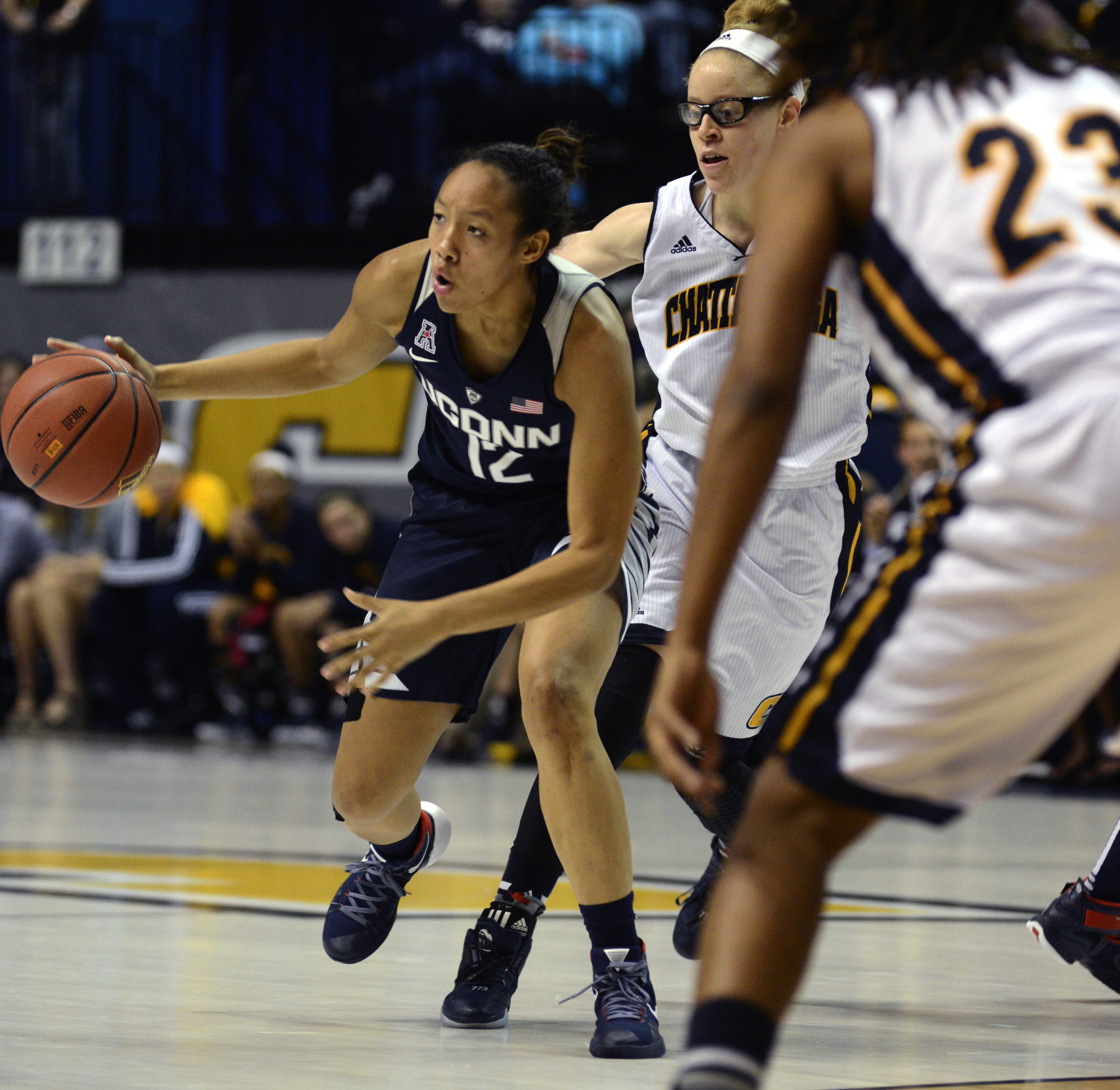 Connecticut's Saniya Chong (12) drives the ball against Chattanooga's Alicia Payne (1) and Moses Johnson (23) in the second half of an NCAA college basketball game Monday, Nov. 30, 2015, in Chattanooga, Tenn. (AP Photo/Billy Weeks)