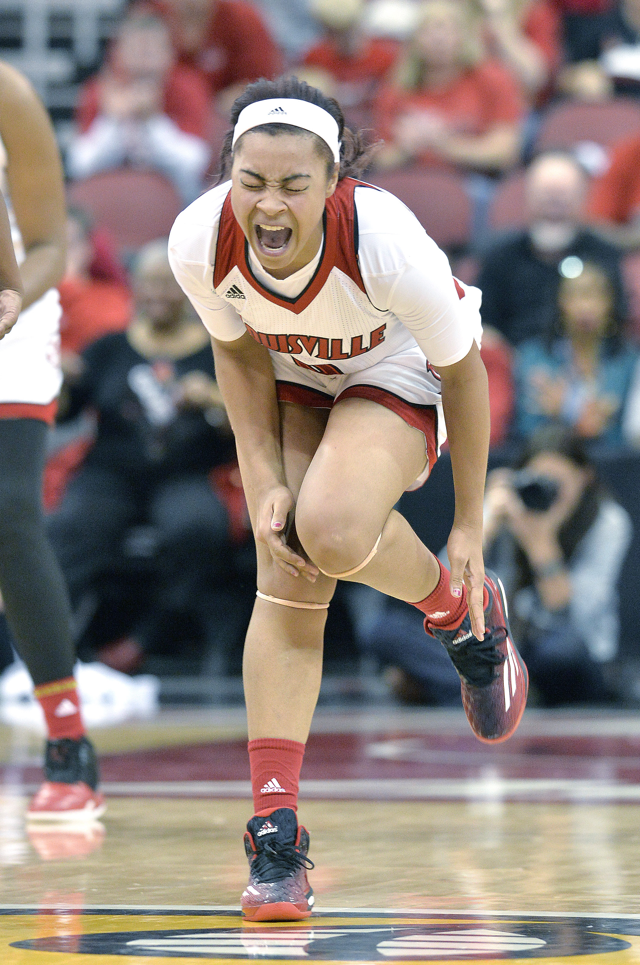 Louisville's Mariya Moore grimaces in pain after twisting her ankle during the second half of an NCAA college basketball game against California, Sunday, Nov. 15, 2015, in Louisville, Ky. California won 75-71. (AP Photo/Timothy D. Easley)