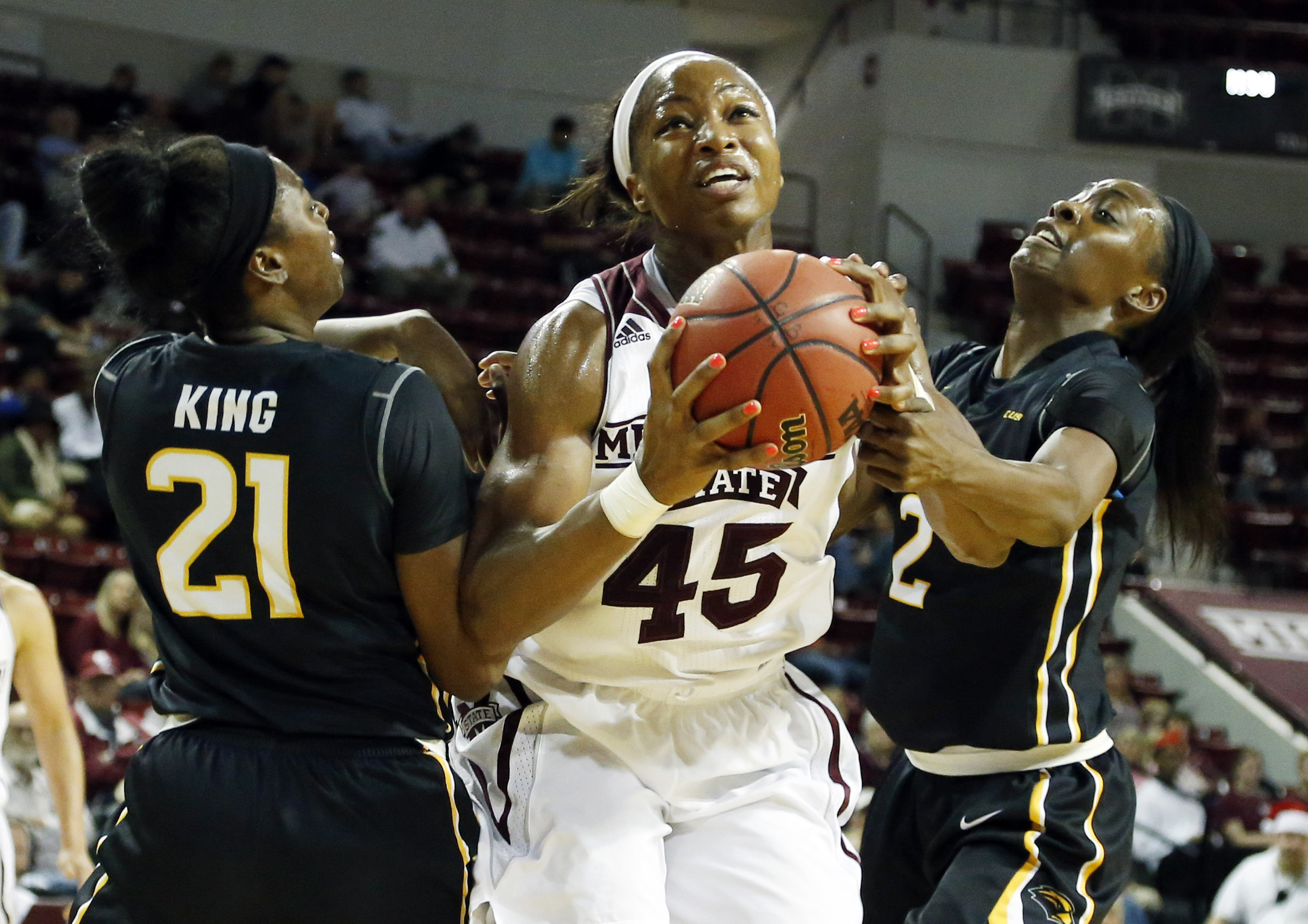 Mississippi State center Chinwe Okorie (45) attempts a layup between Southern Mississippi guard Jayla King (21) and forward Lashyra Cotton (2) in the first half of an NCAA college basketball game in Starkville, Miss., Wednesday, Dec. 16, 2015. (AP Photo/R