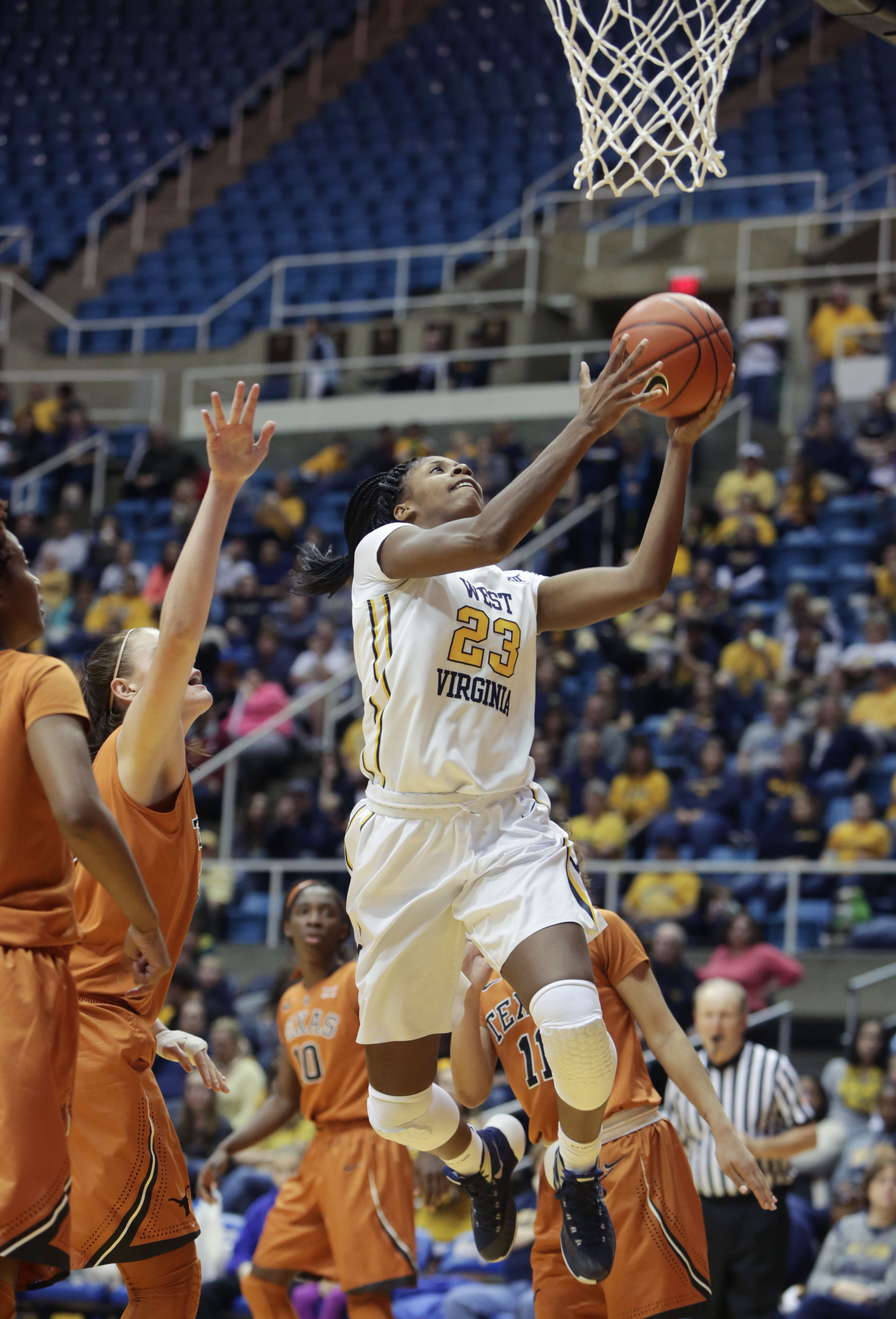 West Virginia guard Bria Holmes (23) scores a basket after driving by Texas center Kelsey Lang (40) during the third period of an NCAA college basketball game, Wednesday, Dec, 30, 2015, in Morgantown, W.Va. (AP Photo/Raymond Thompson)