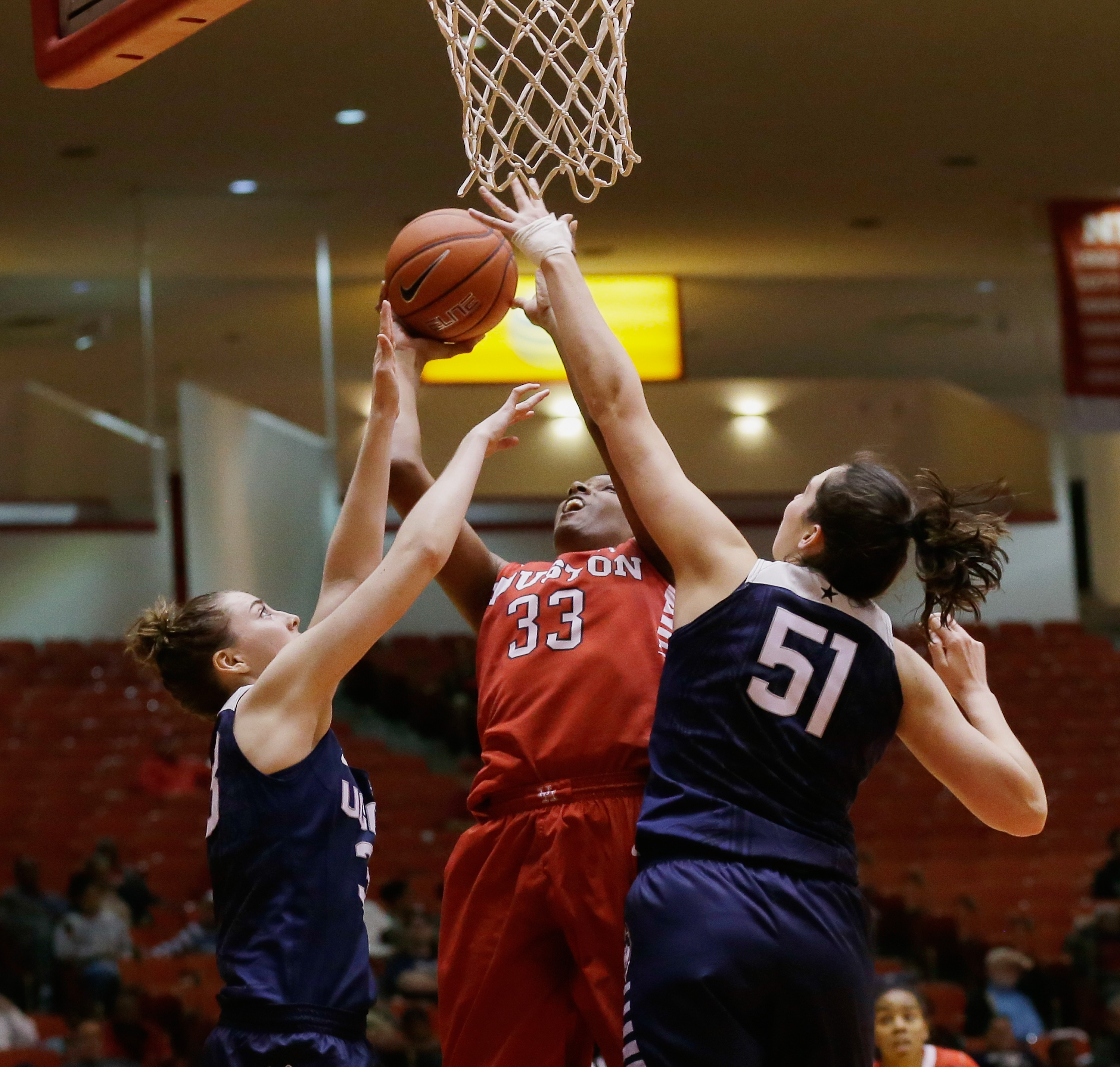 Houston forward Tyler Gilbert (33) shoots over Connecticut guard/forward Katie Lou Samuelson, left, and center Natalie Butler (51) during the second half of an NCAA college basketball game Friday, Jan. 8, 2016, in Houston. Connecticut won 76-37. (AP Photo