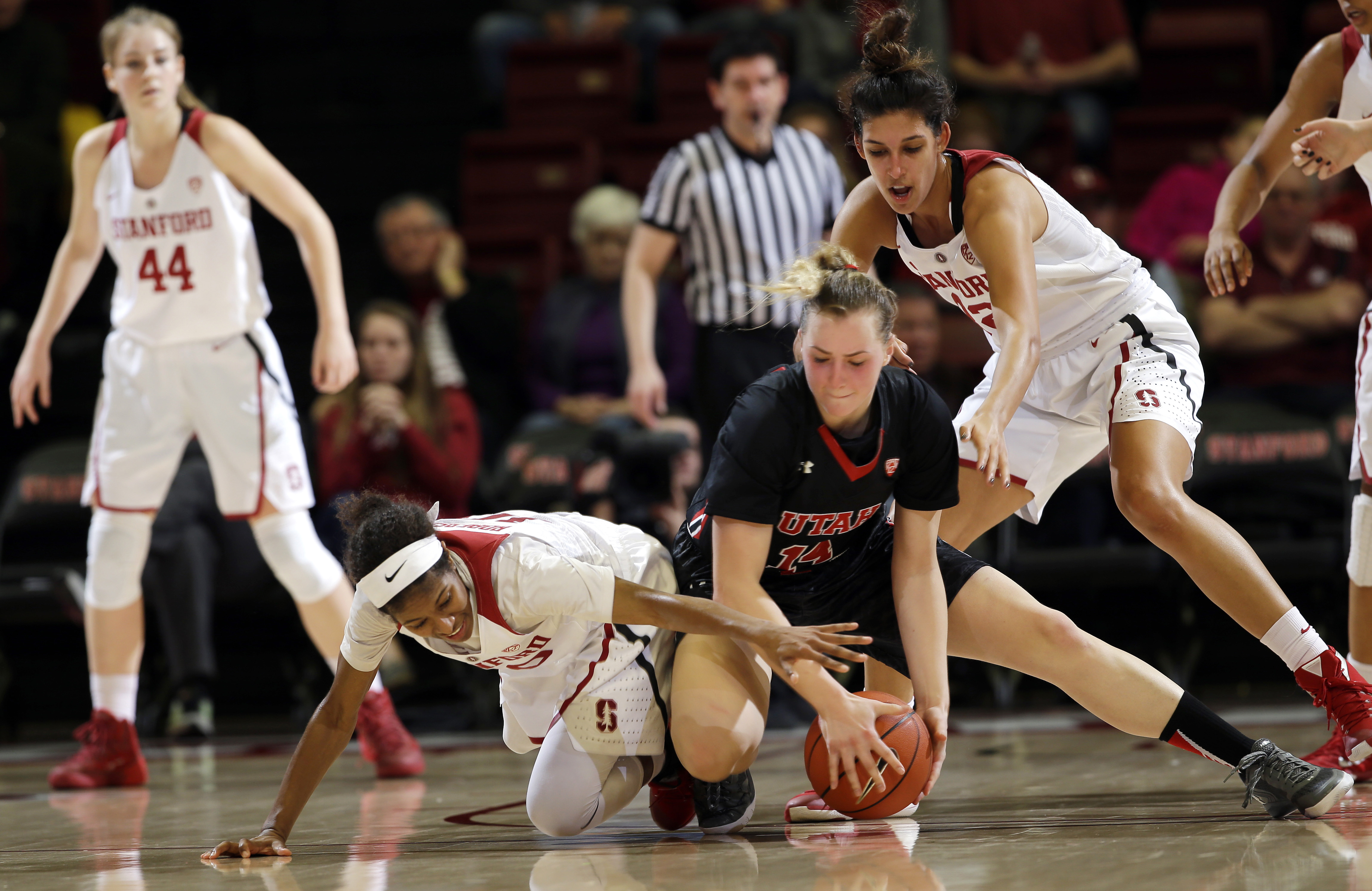 Utah guard Paige Crozon, center, grasps the ball between Stanford guard Briana Roberson, left, and forward Kailee Johnson, right, during the second half of an NCAA college basketball game Friday, Jan. 8, 2016, in Stanford, Calif. Stanford won 72-52. (AP P