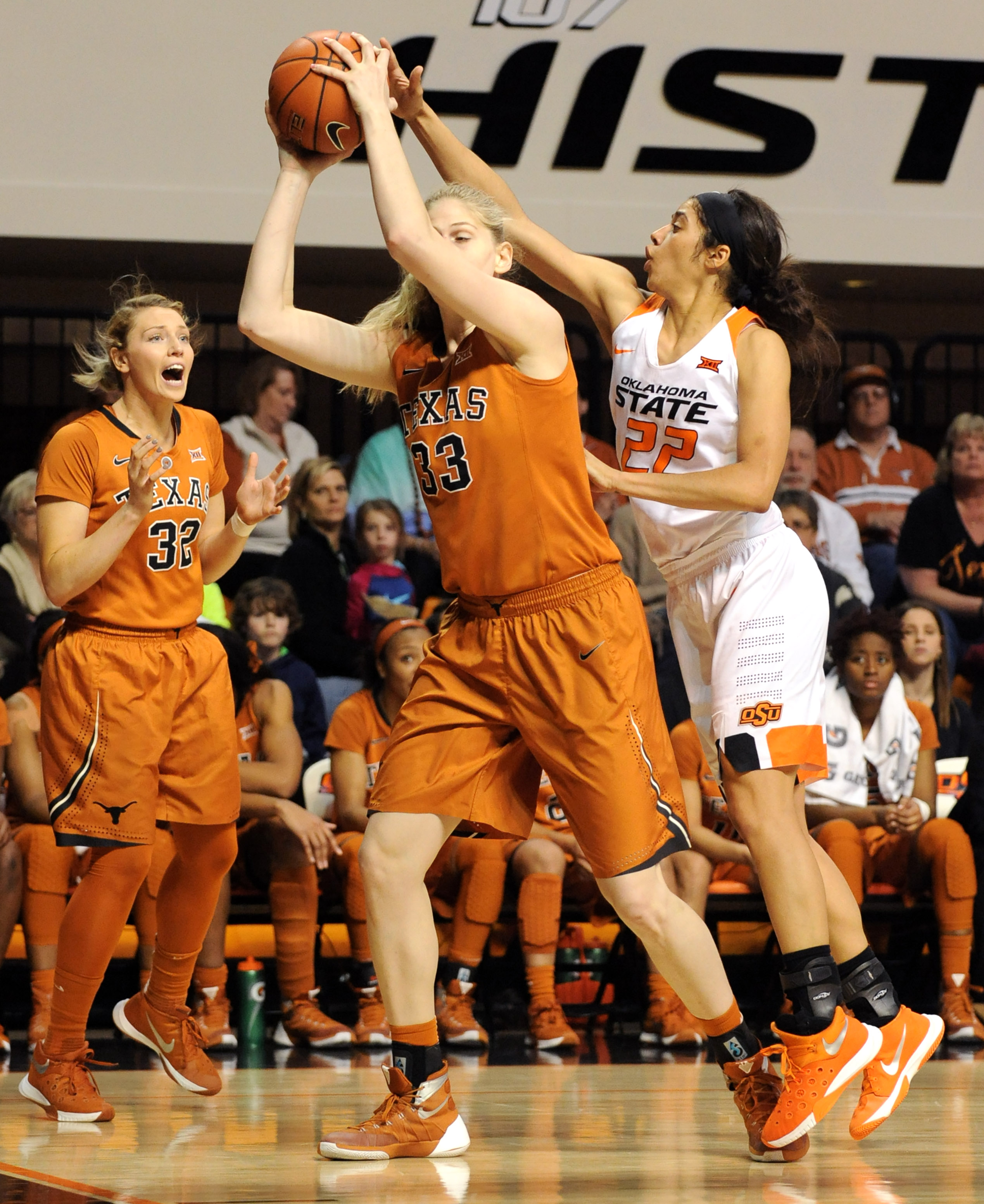 Texas guard Brady Sanders (32) reacts to Oklahoma State guard Brittney Martin (22) reaching over the back of Texas forward Sara Hattis (33) during the second half of an NCAA college basketball game in Stillwater, Okla., Saturday, Jan. 9, 2016. Martin had