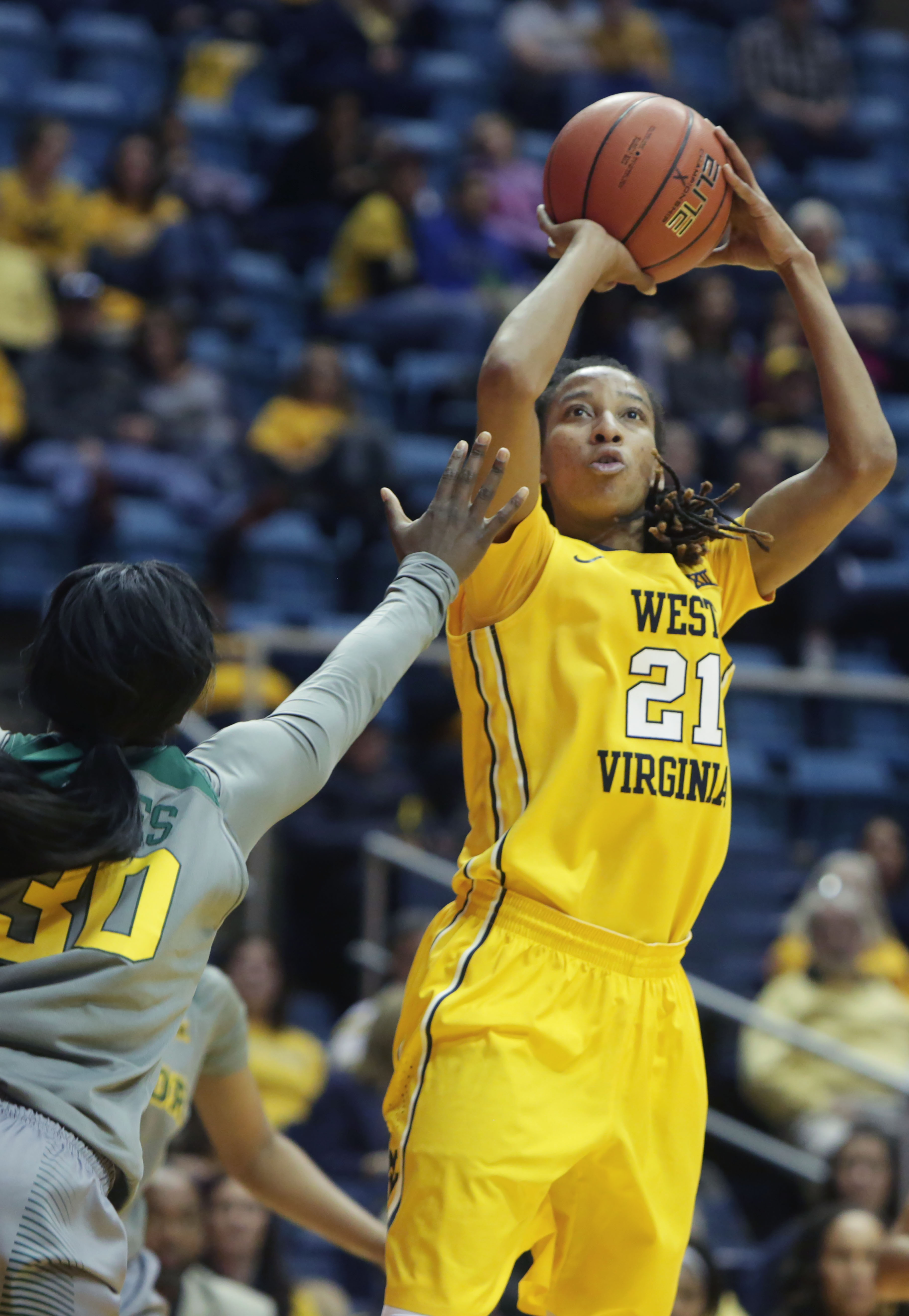 West Virginia guard Jessica Morton (21) takes a shot while being guarded by Baylor guard Alexis Jones (30) during the second half of an NCAA college basketball game, Saturday, Jan, 30, 2016, in Morgantown, W.Va. (AP Photo/Raymond Thompson)
