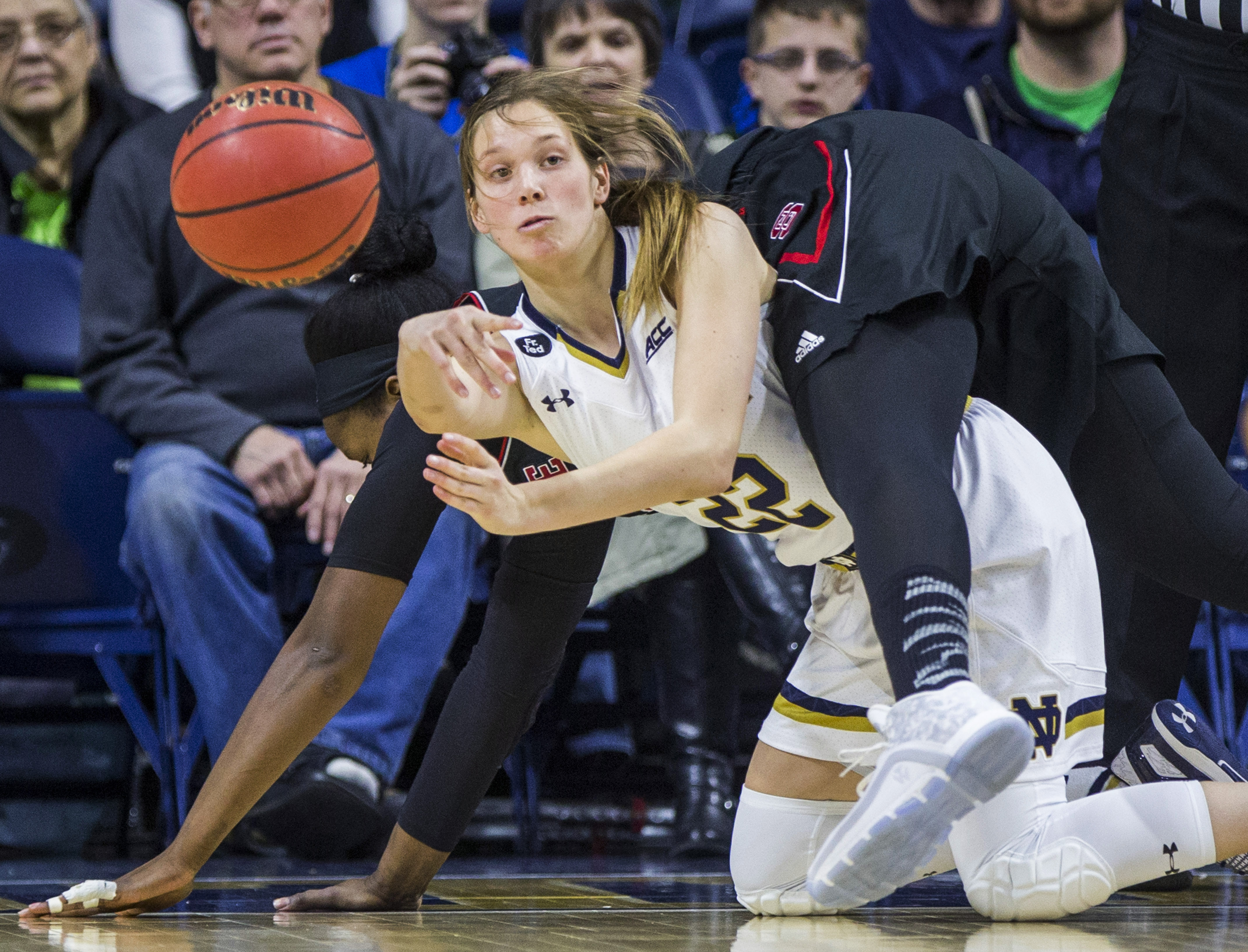 Notre Dame's Madison Cable (22) passes the ball as North Carolina State's Jennifer Mathurin (11) falls onto her during the first half of an NCAA college basketball game Thursday, Feb. 4, 2016, in South Bend, Ind. (AP Photo/Robert Franklin)