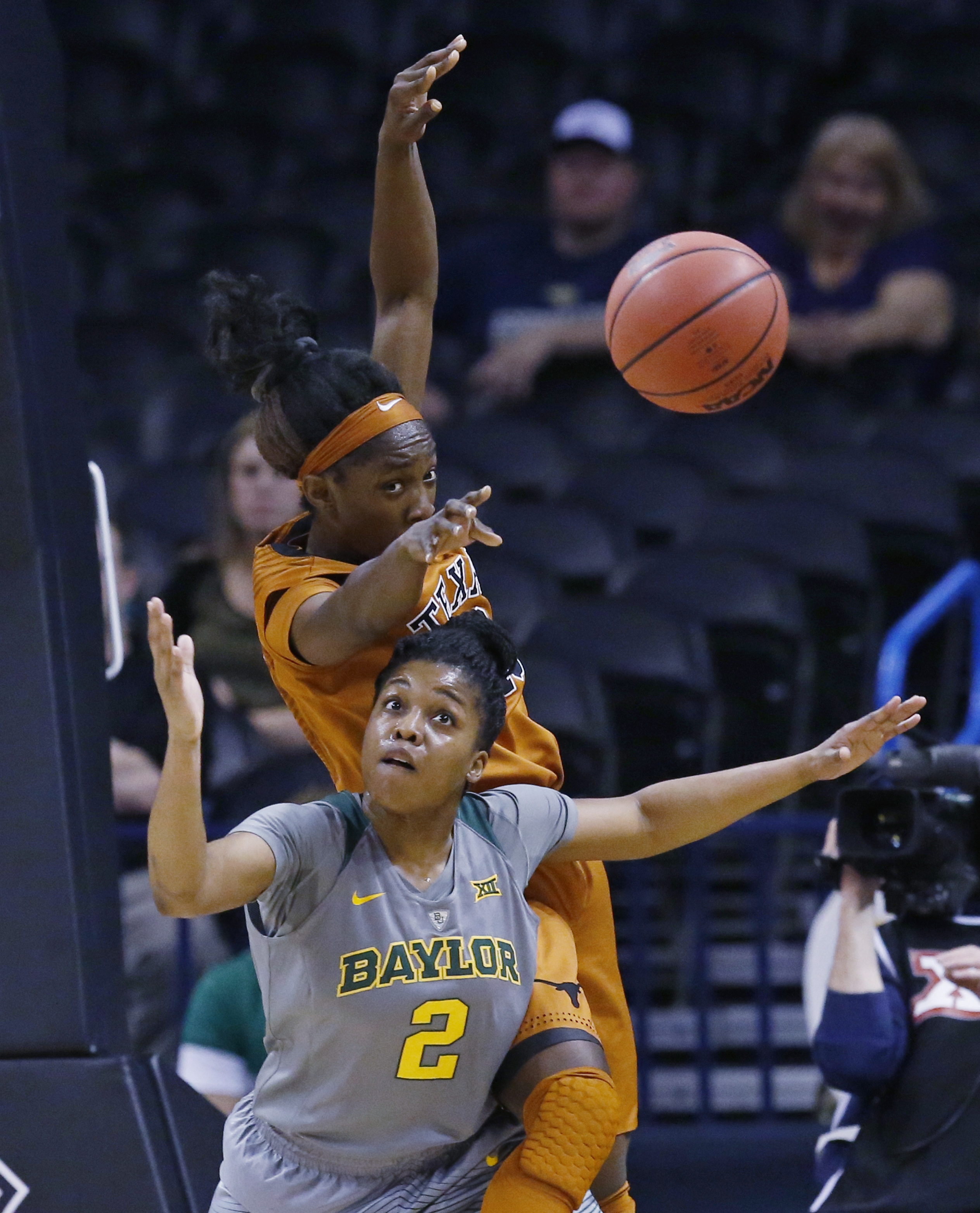 Texas guard Lashann Higgs, rear, and Baylor guard Niya Johnson (2) reach for a loose ball in the first quarter of an NCAA college basketball championship game in the Big 12 women's tournament in Oklahoma City, Monday, March 7, 2016. (AP Photo/Sue Ogrocki)