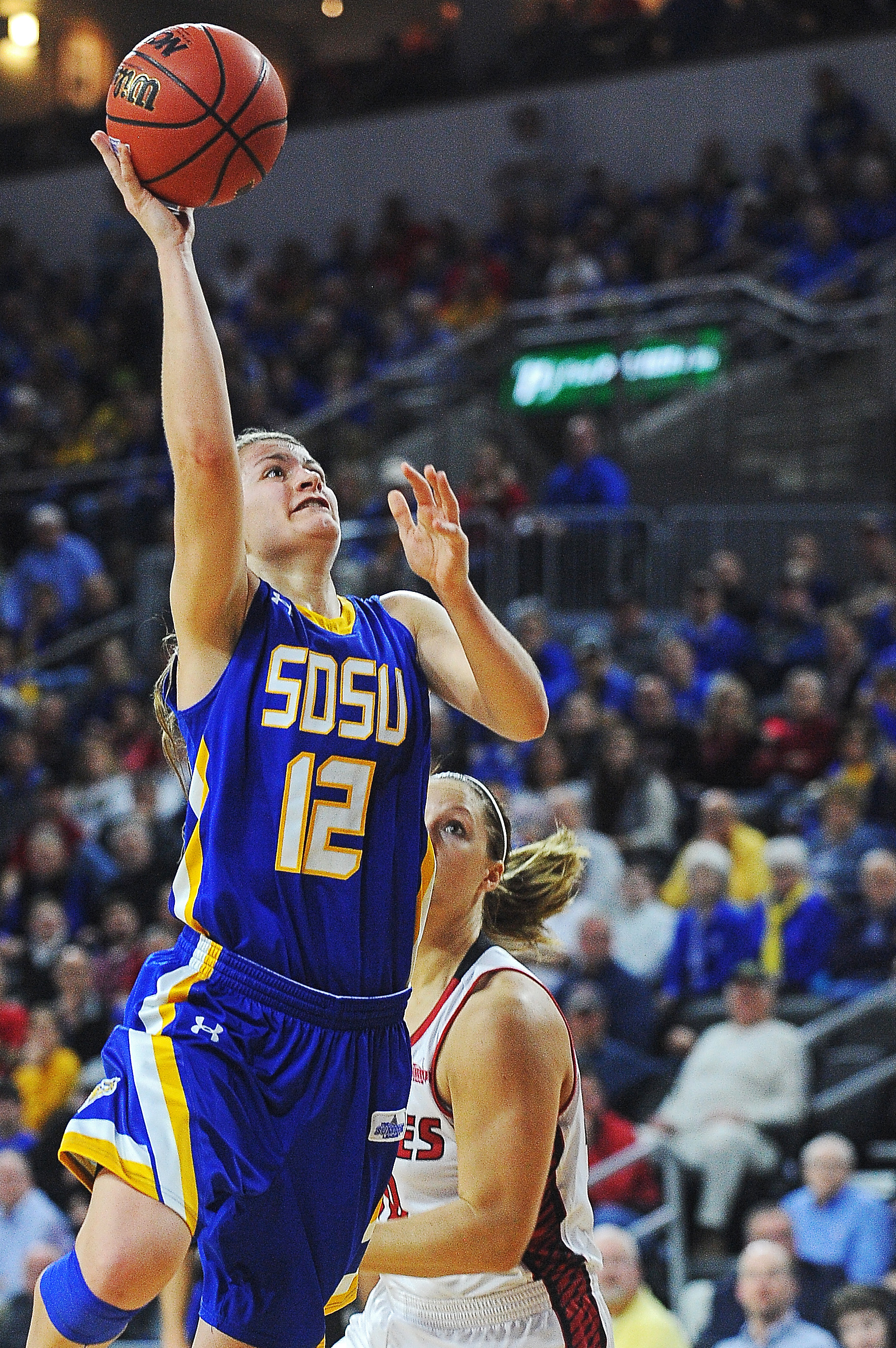 South Dakota State's Macy Miller (12) goes up for a shot in front of South Dakota's Margaret McCloud (30) during the Summit League championship NCAA college basketball game, Tuesday, March 8, 2016, at the Denny Sanford Premier Center in Sioux Falls, S.D.