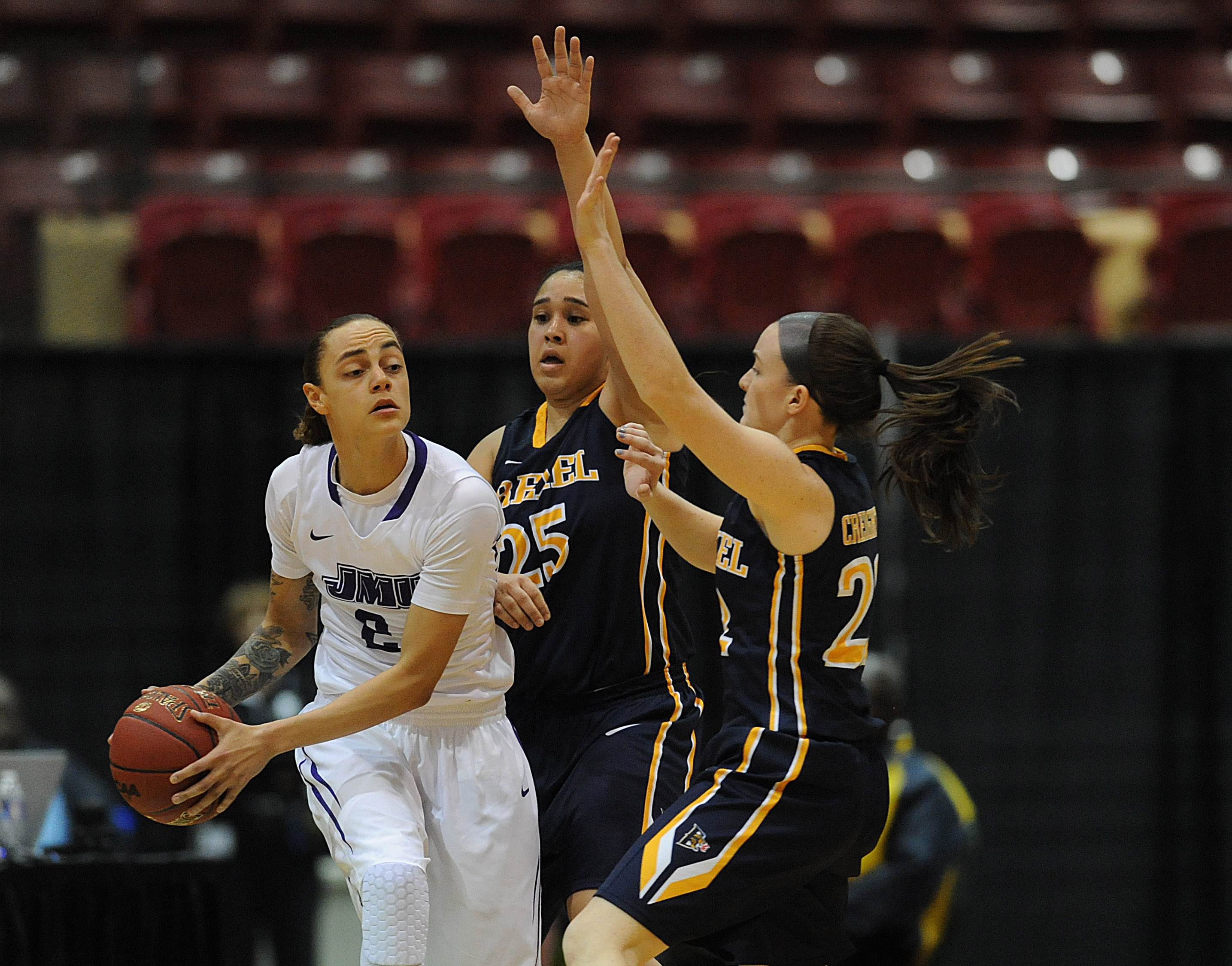 James Madison's Destiny Jones, left, looks to pass under pressure from  Drexel's  Meghan Creighton,, right, and Kelsi Lidge in the first half of an NCAA college basketball game in the championship of the Colonial Athletic Association women's tournament, S