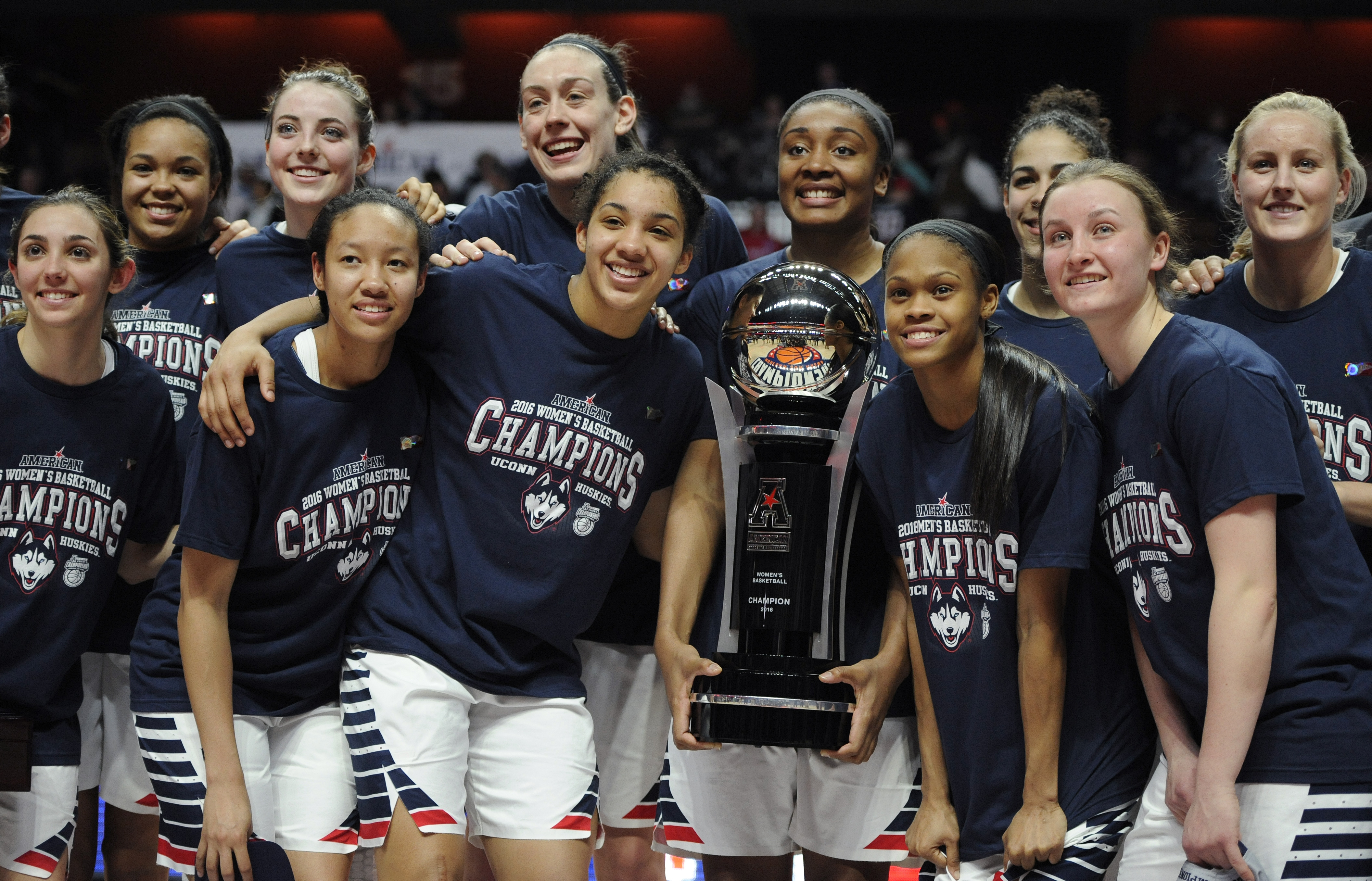 FILE- In this March 7, 2016, file photo, Connecticut players pose with the championship trophy at the end of a NCAA college basketball game in the American Athletic Conference tournament finals against South Florida at Mohegan Sun Arena in Uncasville, Con