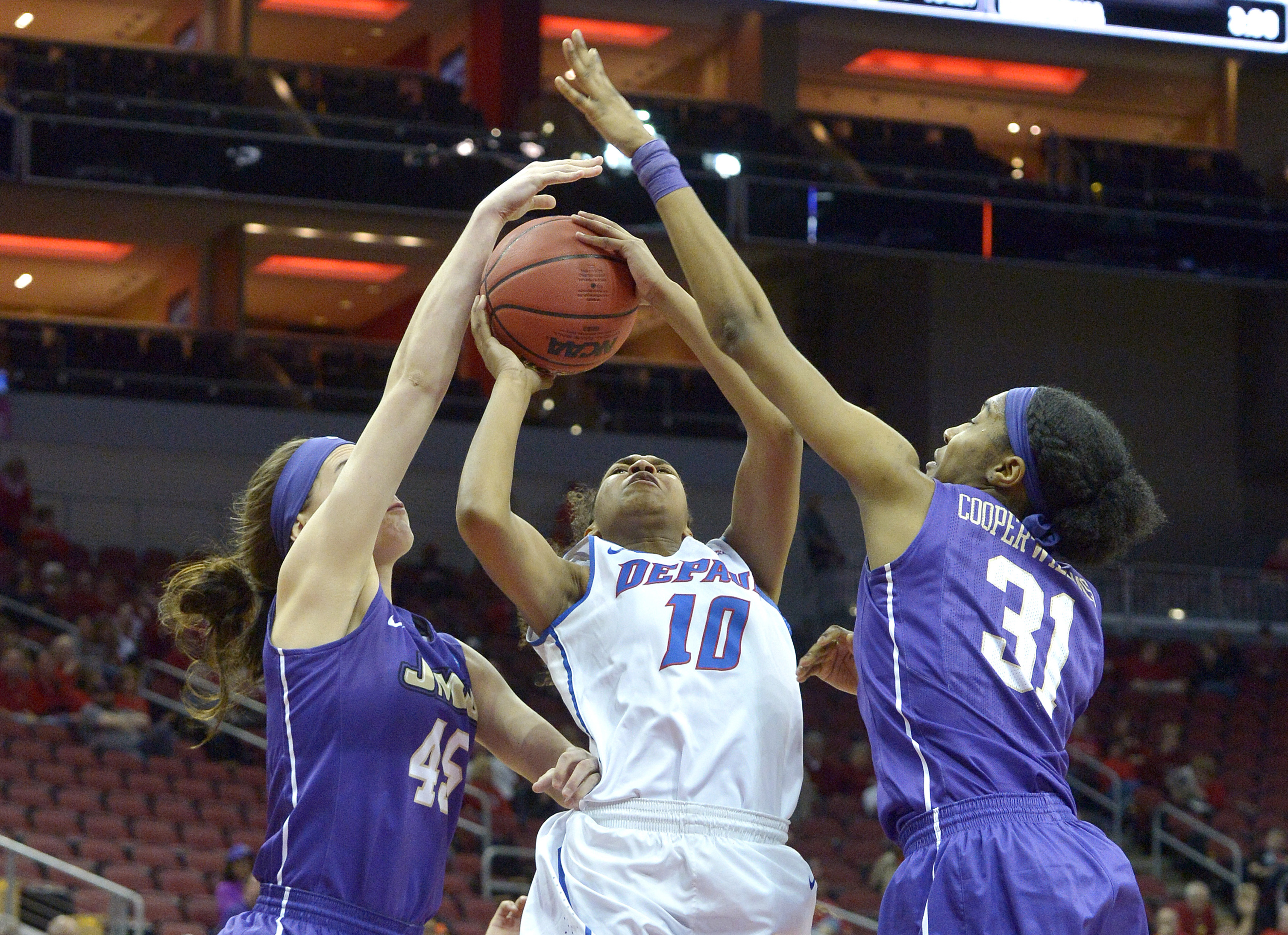 DePaul's Amarah Coleman (10) attempts a shot through the defense of James Madison's Kayla Cooper-Williams (31) and Savannah Felgemacher (45) during the second half of a first-round women's college basketball game in the NCAA Tournament in Louisville, Ky.,