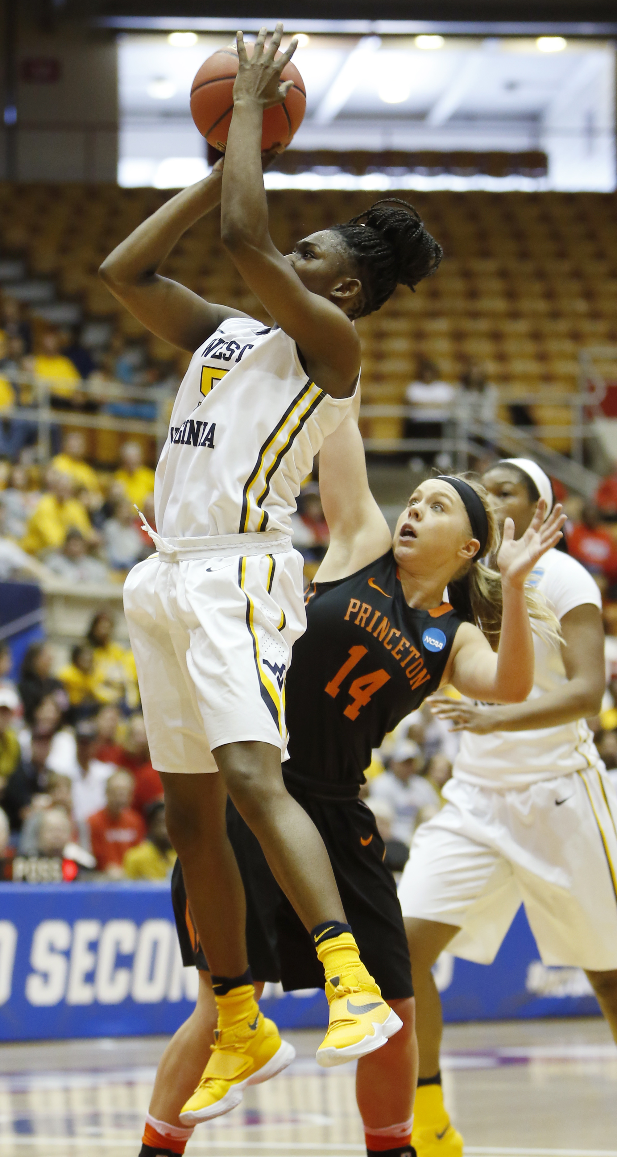 West Virginia's Tynice Martin, left, shoots the ball after dribbling past Princeton's Amanda Berntsen during a first-round women's college basketball game in the NCAA Tournament Friday, March 18, 2016, in Columbus, Ohio. West Virginia beat Princeton 74-65