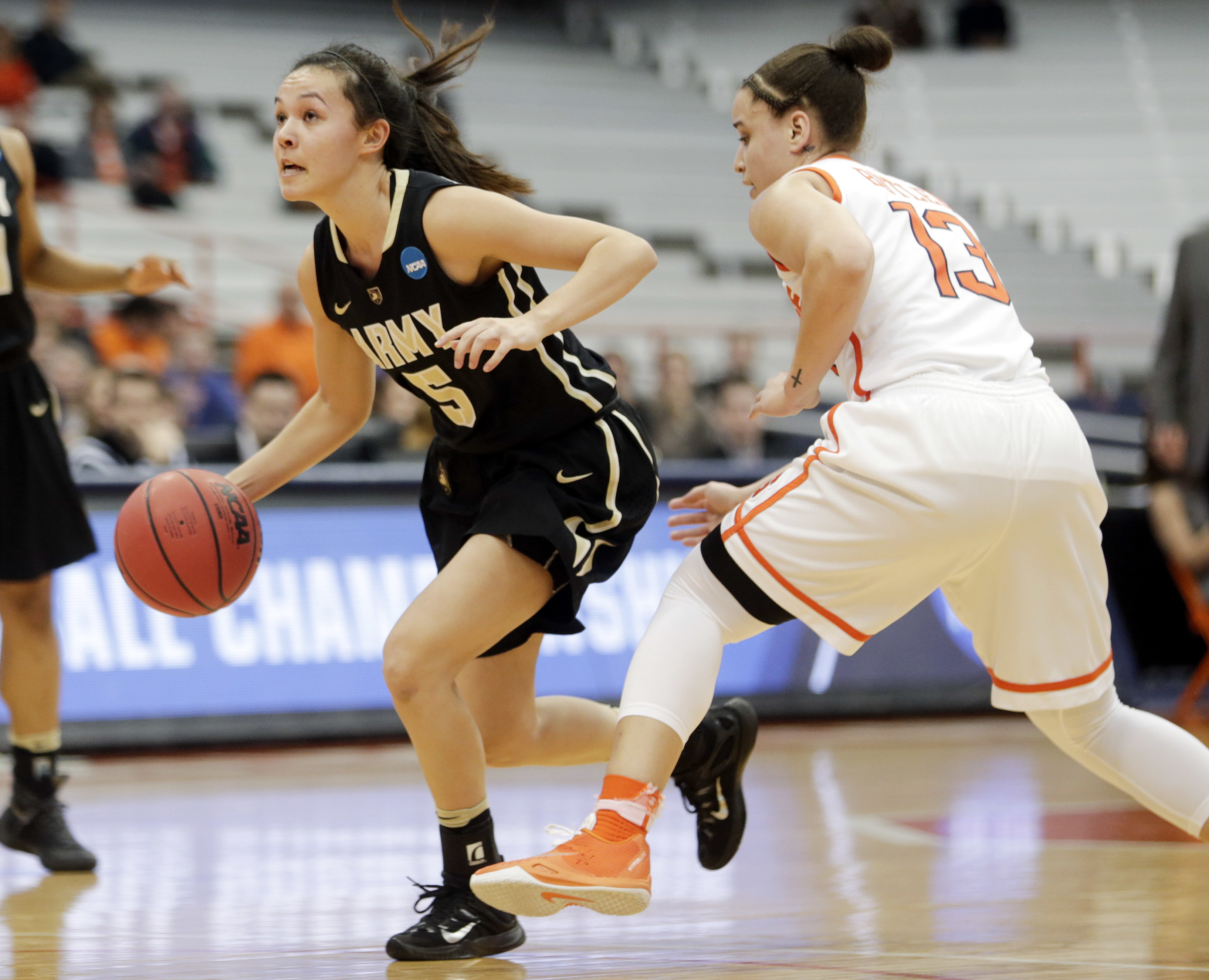 Army guard Kelsey Minato (5) drives past Syracuse guard Brianna Butler (13) during the first half of a first-round women's college basketball game in the NCAA Tournament on Friday, March 18, 2016, in Syracuse, N.Y. (AP Photo/Mike Groll)