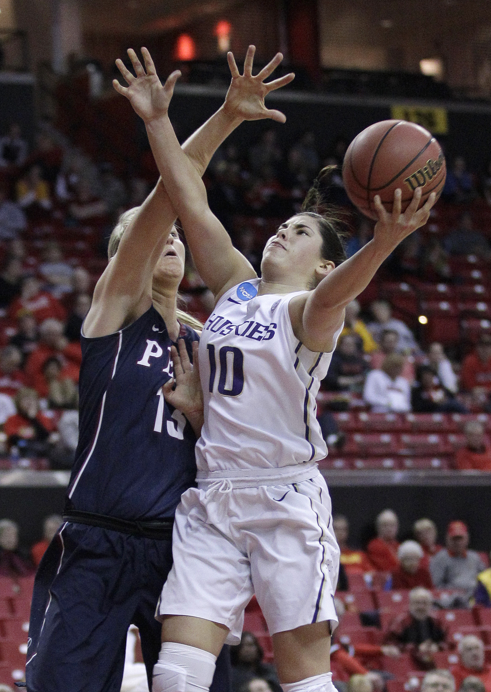 Washington guard Kelsey Plum, right, shoots against Penn center Sydney Stipanovich in the first half of an NCAA college basketball game in the first round of the NCAA tournament, Saturday, March 19, 2016, in College Park, Md. (AP Photo/Patrick Semansky)