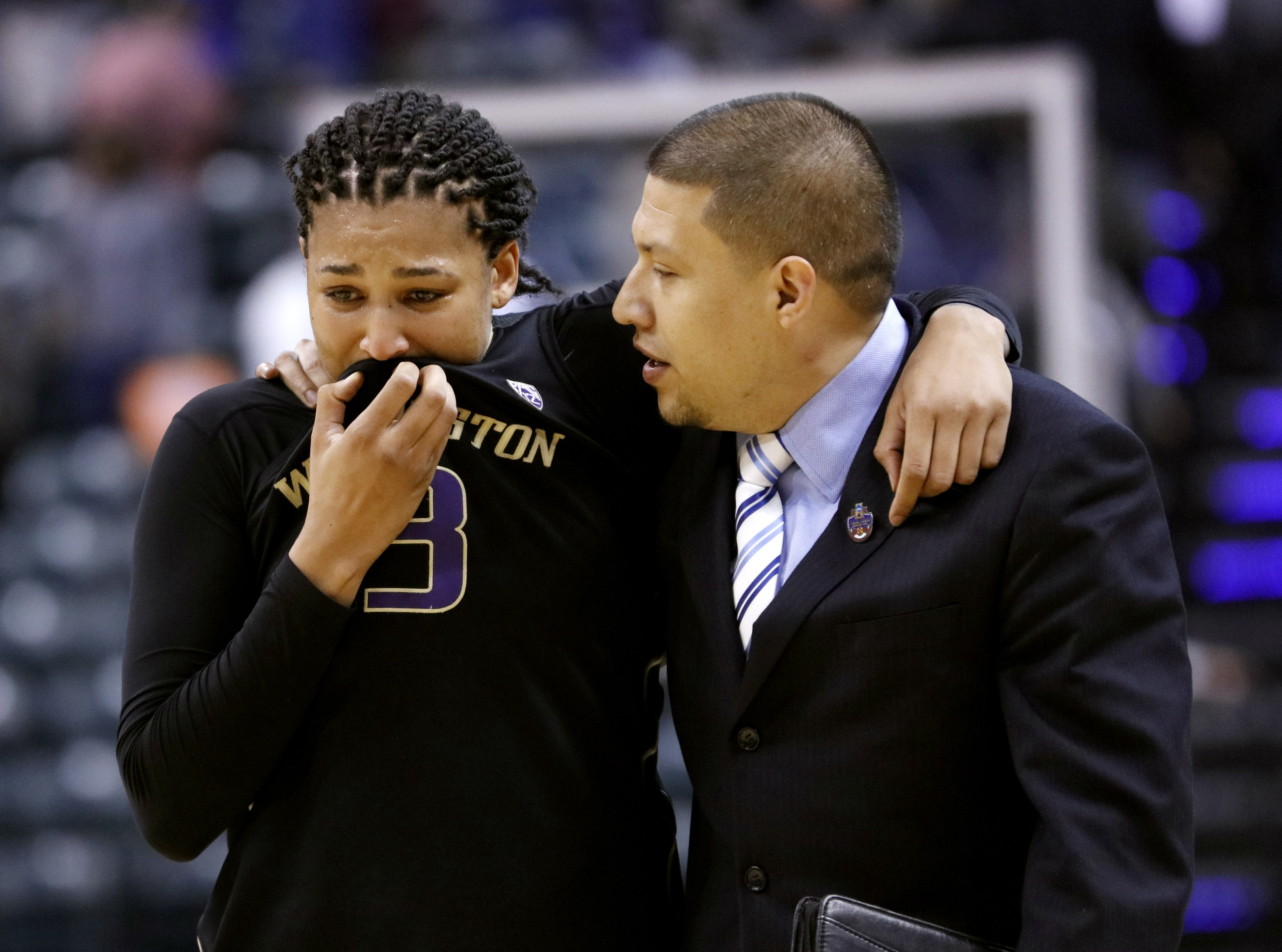 Washington's Talia Walton (3) is comforted by assistant coach Fred Castro following a national semifinal game against Syracuse, at the women's Final Four in the NCAA college basketball tournament Sunday, April 3, 2016, in Indianapolis. Syracuse won 80-59.