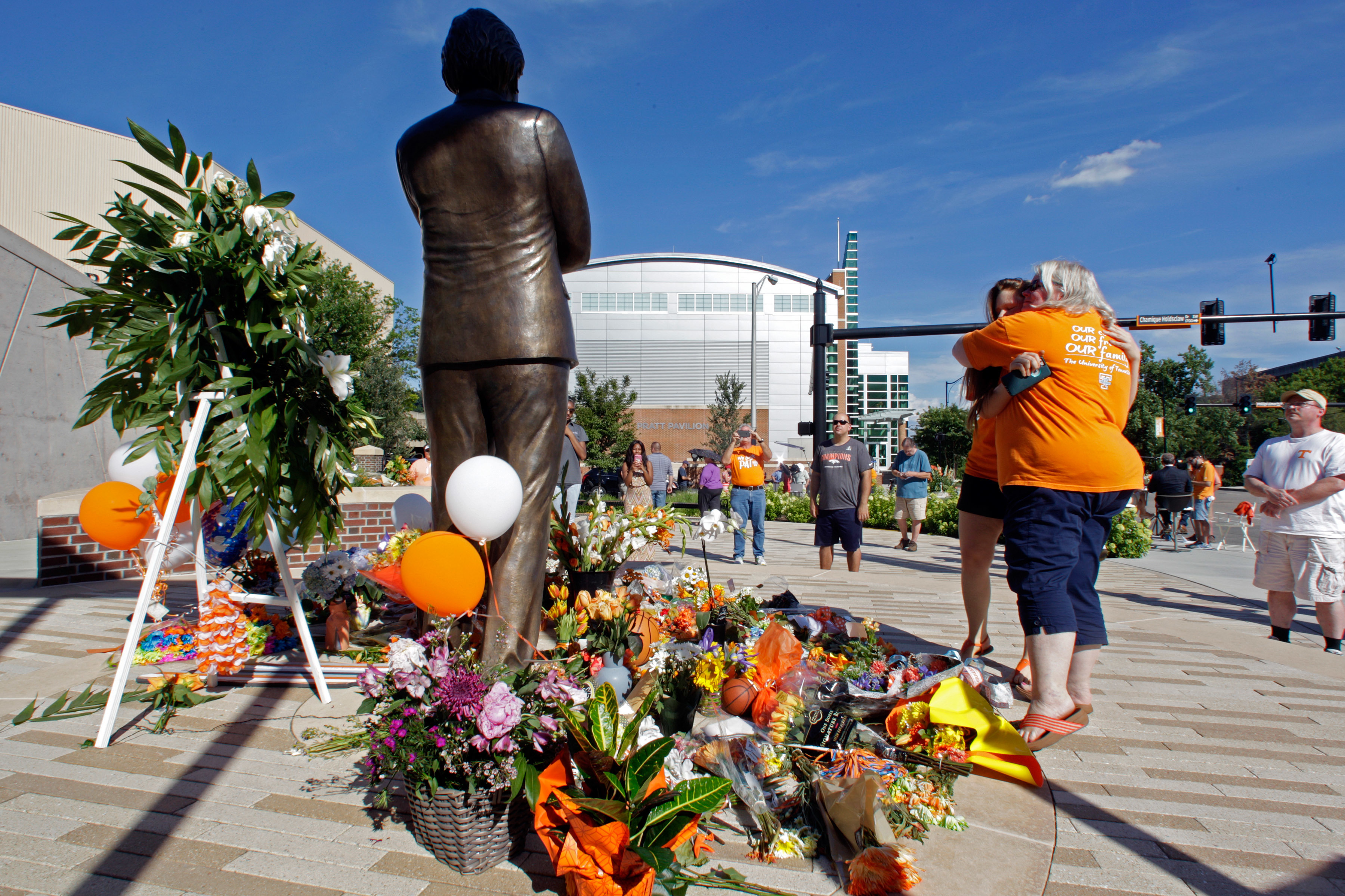 Susan Reel, right, hugs Becca Bowen near the memorial at Pat Summitt Plaza on Tuesday, June 28, 2016, in Knoxville, Tenn. Summitt, the winningest coach in Division I college basketball history who uplifted the women's game from obscurity to national promi