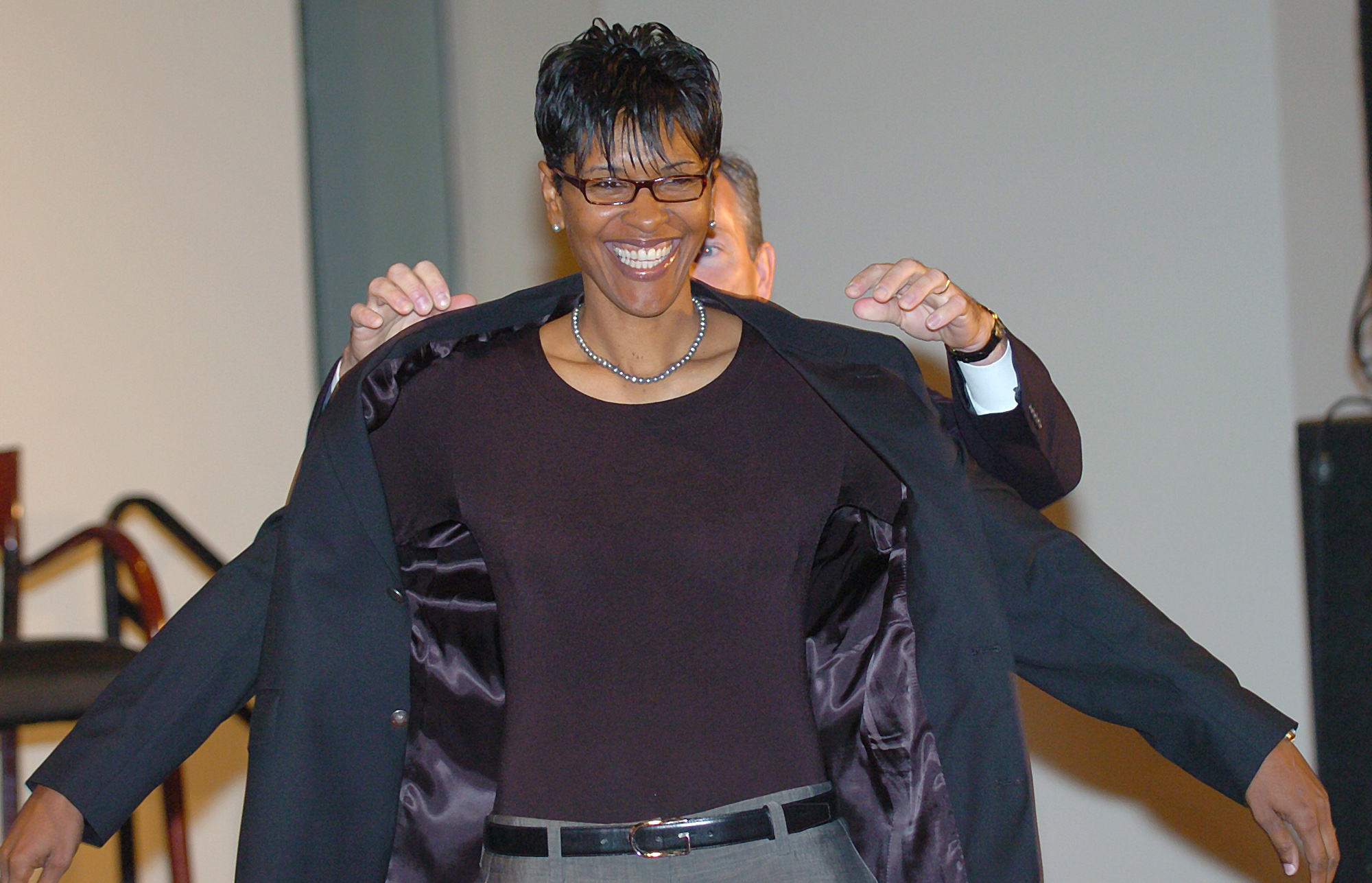Lynette Woodard smiles as John L. Doleve, president and CEO of the Basketball Hall of Fame helps her put on her Hall of Fame jacket at a news conferernce at the Hall of Fame in Springfield, Mass., Friday, Sept. 10, 2004. Woodard is an Olympic gold medalis