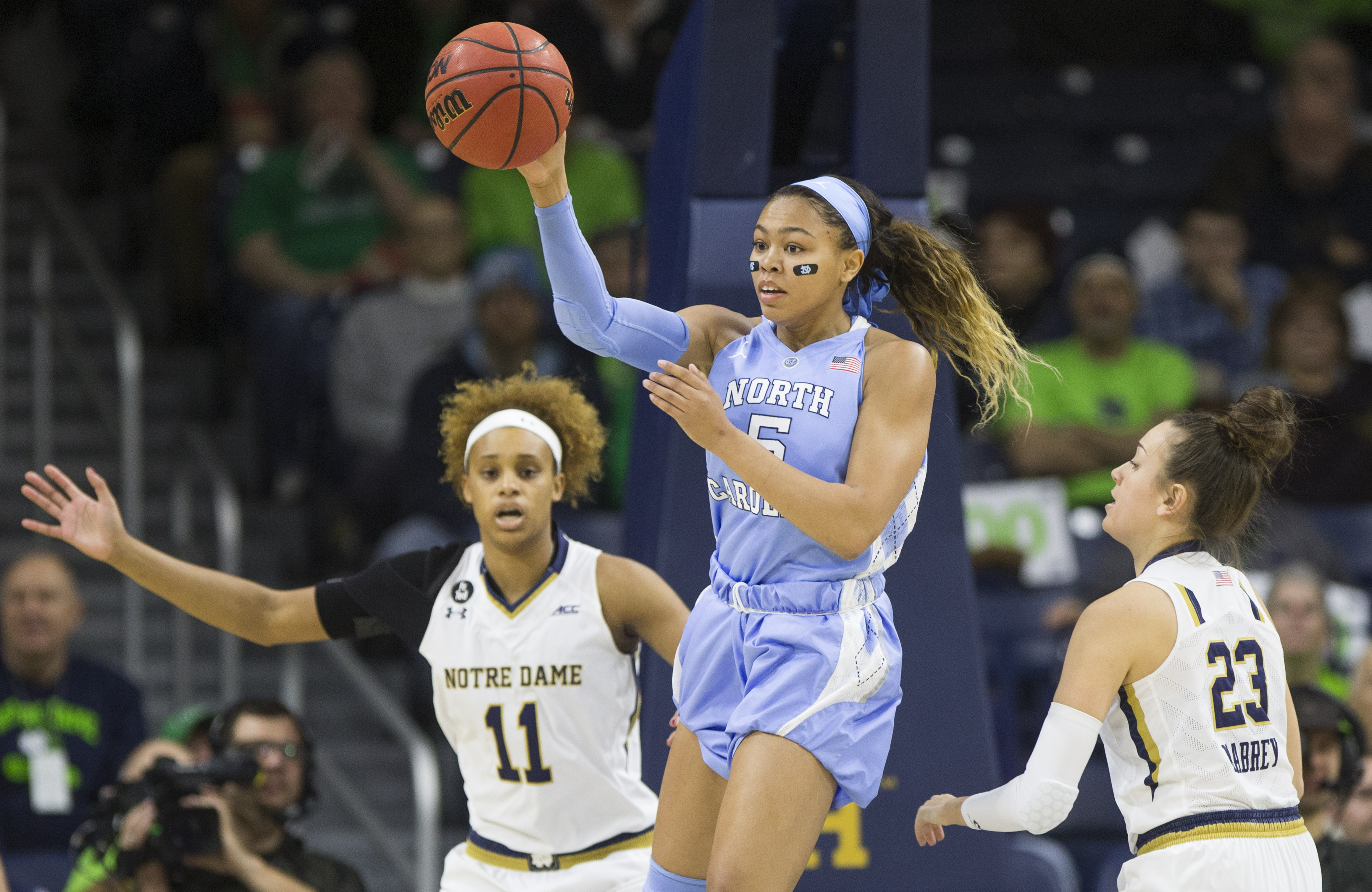 North Carolinas Stephanie Watts (5) passes the ball next to Notre Dames Brianna Turner (11) and Michaela Mabrey (23) during the first half of an NCAA college basketball game on Sunday, Jan. 10, 2016, in South Bend, Ind. (AP Photo/Robert Franklin)