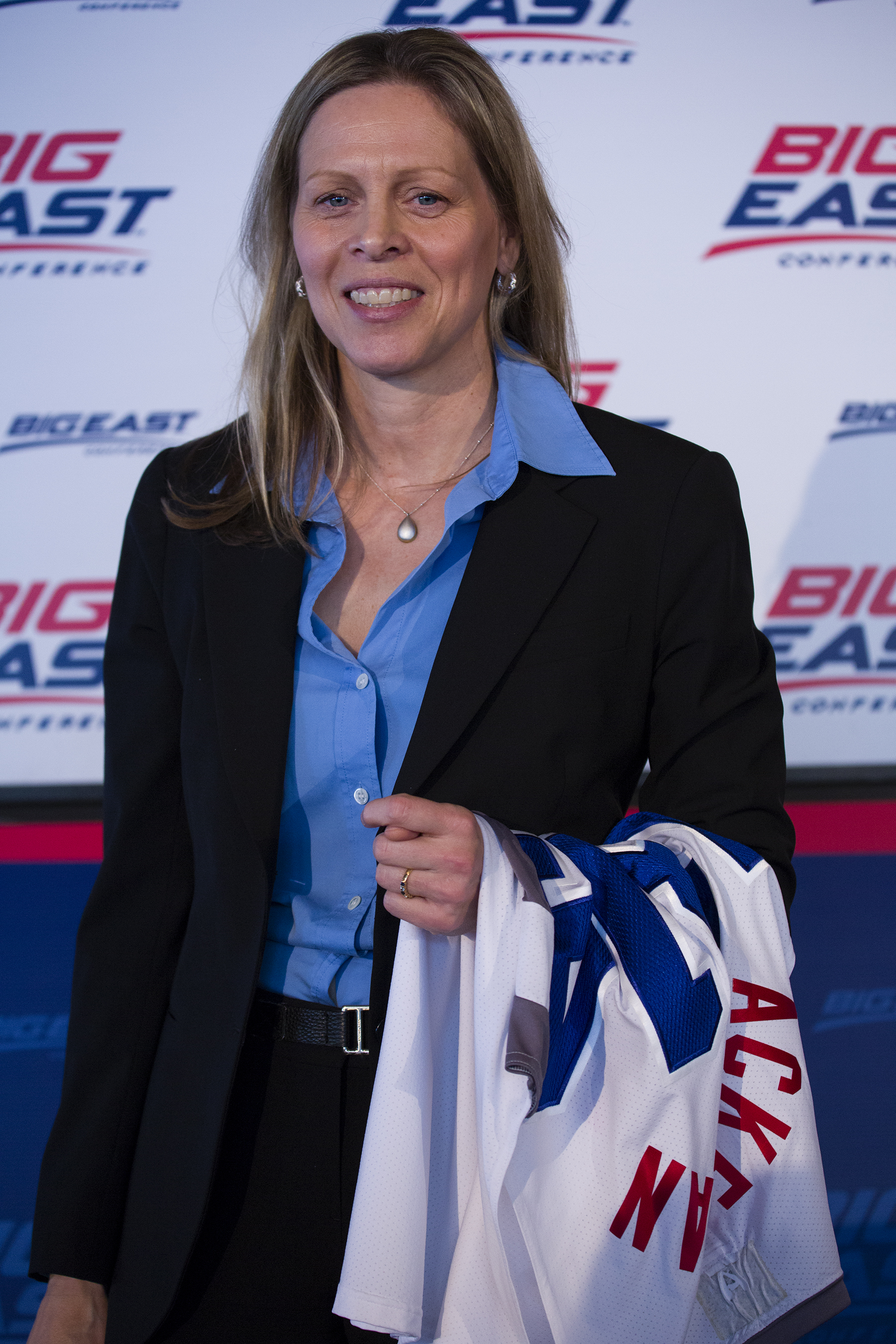 Big East Commissioner Val Ackerman stands with a jersey after a news conference during the Big East Conference NCAA college basketball media dayin New York, Wednesday, Oct. 16, 2013. (AP Photo/Craig Ruttle)