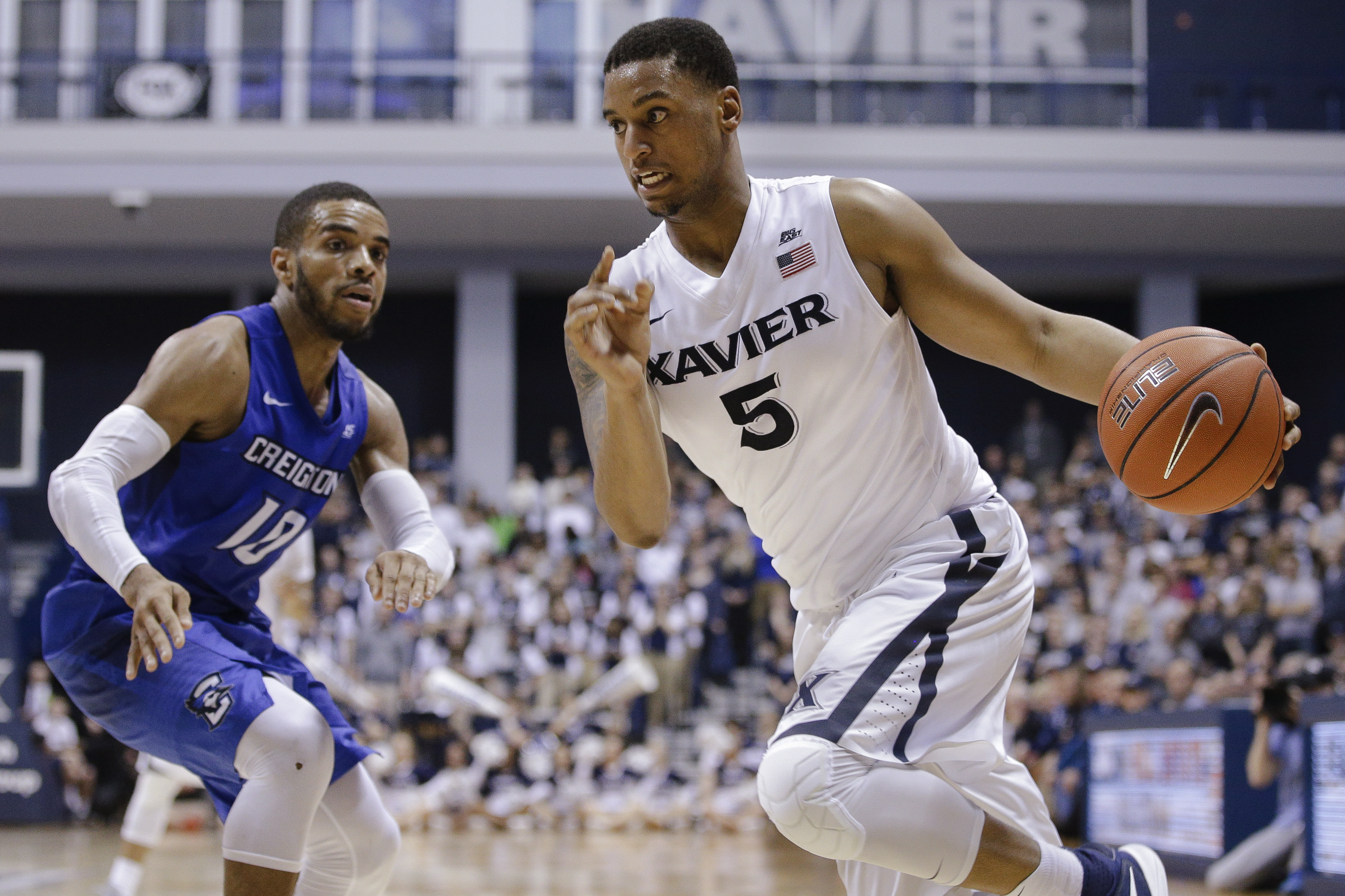FILE - In this March 5, 2016, file photo, Xavier's Trevon Bluiett (5) drives past Creighton's Maurice Watson Jr. during an NCAA college basketball game in Cincinnati. No. 7 Xavier has its highest preseason ranking as it tries to build upon its breakthroug