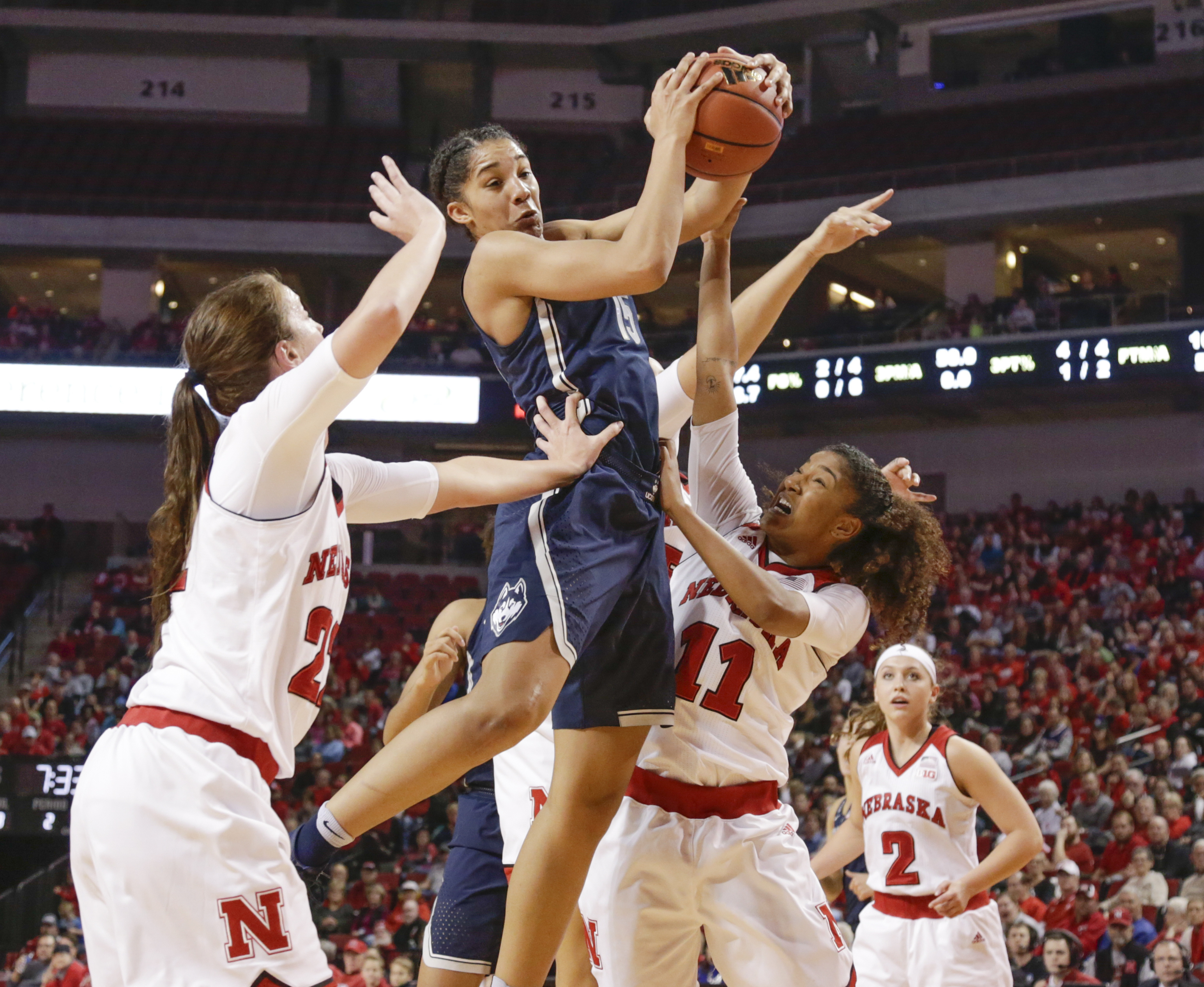 Connecticut's Gabby Williams (15) grabs a rebound between Nebraska's Allie Havers (22) and Esther Ramacieri (11) , with Rylie Cascio Jensen (2) watching, during the first half of an NCAA college basketball game in Lincoln, Neb., Wednesday, Dec. 21, 2016.
