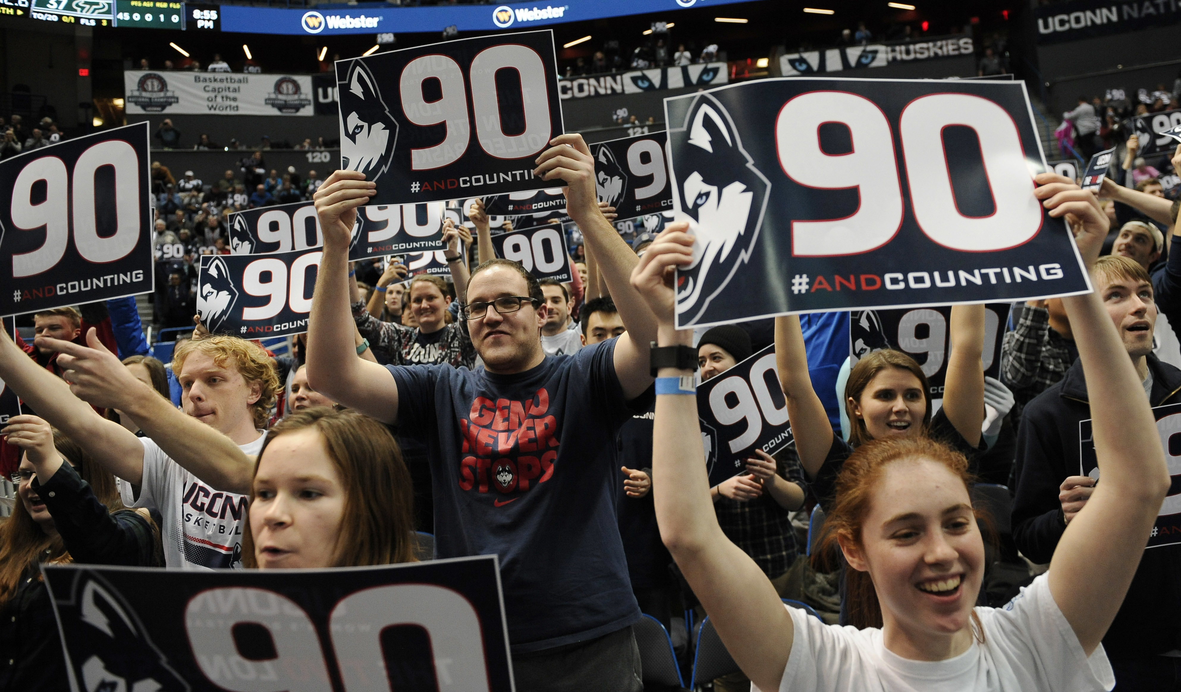 Fans hold up signs for Connecticut's 90 game win streak at the end of an NCAA college basketball game against South Florida, Tuesday, Jan. 10, 2017, in Hartford, Conn. (AP Photo/Jessica Hill)