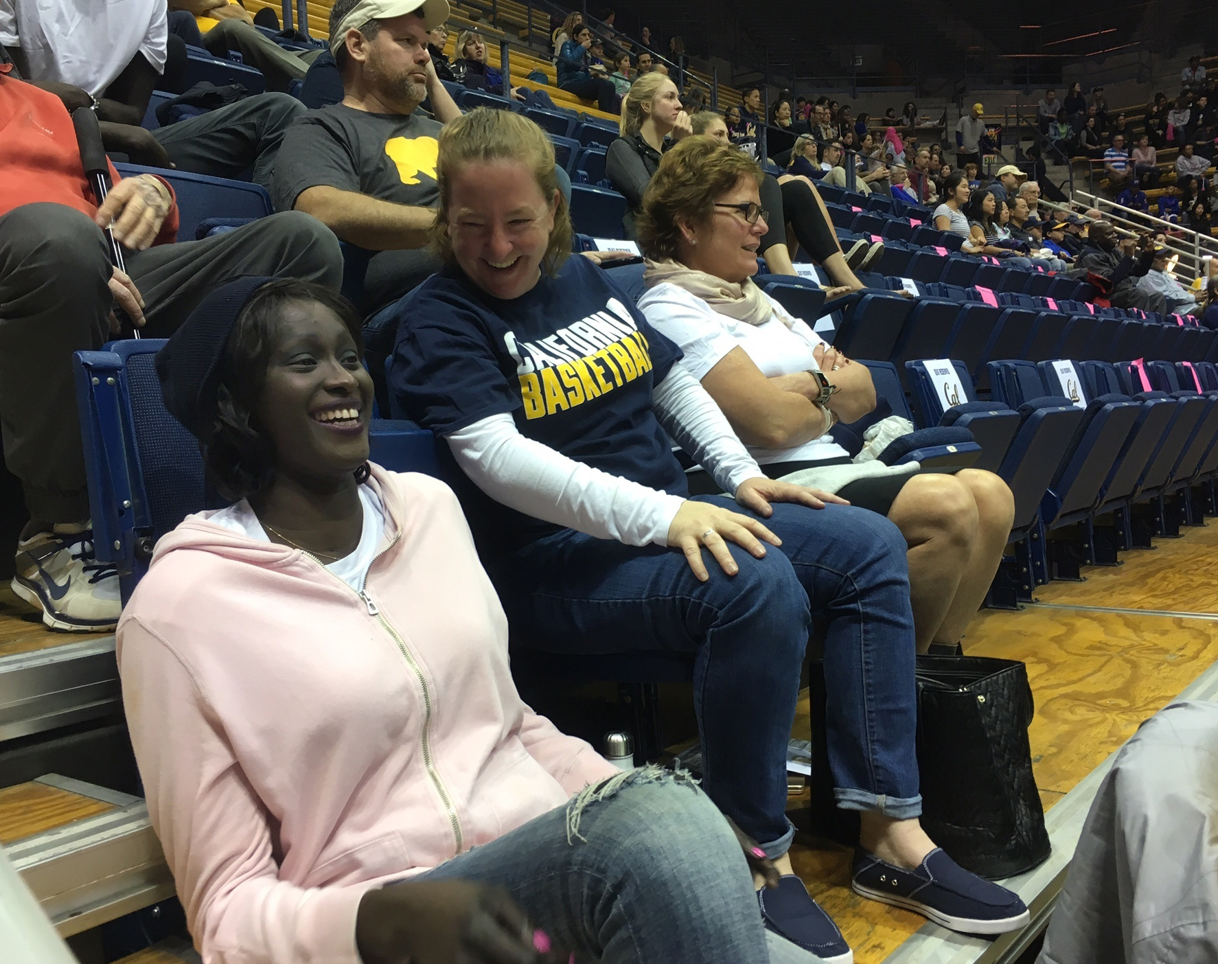 Former California women's basketball player Rama N'diaye, left, and athletic trainer Ann Caslin share a light moment before the NCAA college basketball's California home game with Colorado in Berkeley, Calif., Sunday, Feb. 12, 2017. Diagnosed last July wi