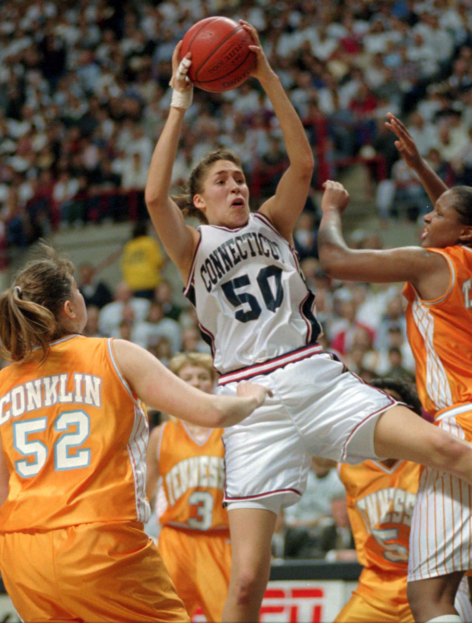 FILE - In this Jan. 16, 1995, file photo, Connecticut's Rebecca Lobo (50) pulls in a rebound as Tennessee's Abby Conklin (52) and Tiffani Johnson, right, defend during the first half of an NCAA college basketball game in Storrs, Conn. No current UConn pla