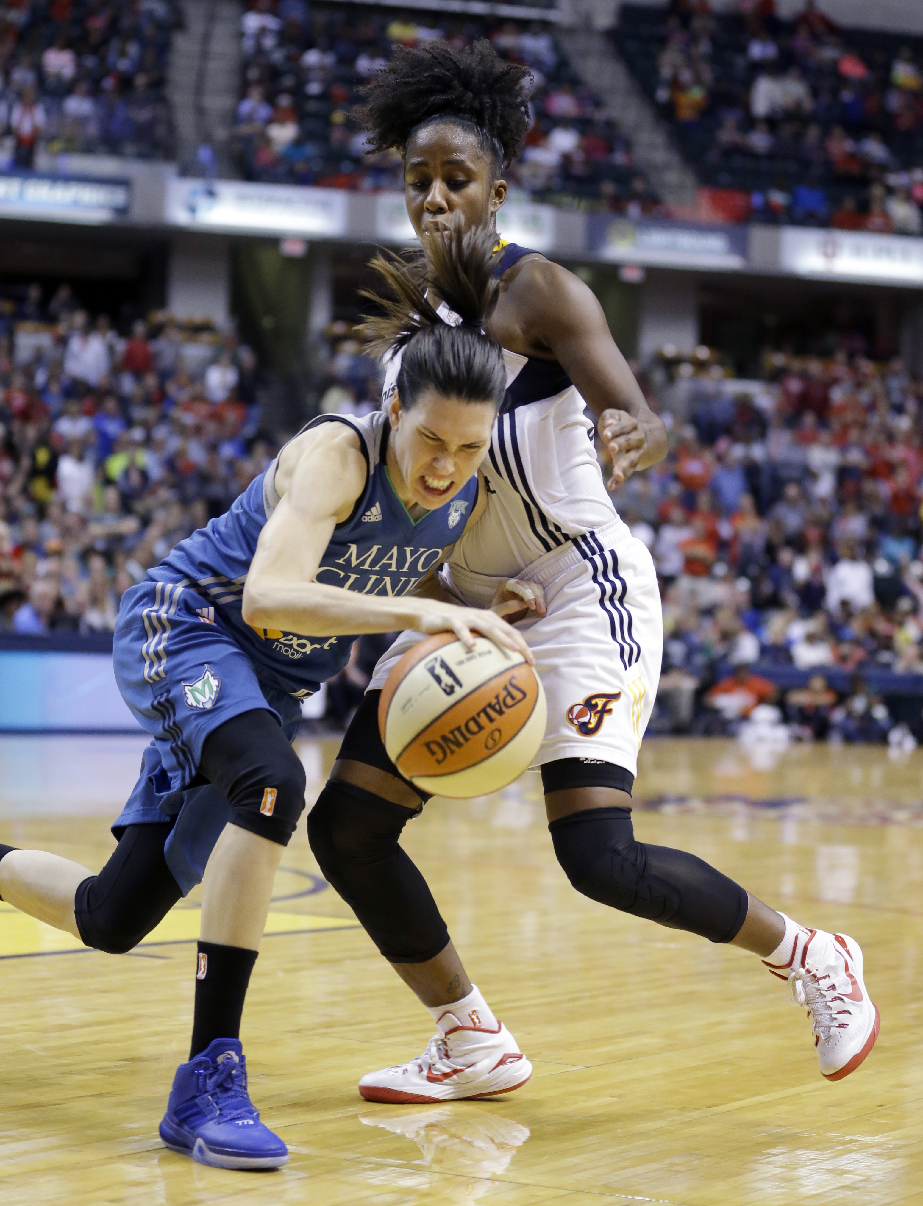 Minnesota Lynx's Anna Cruz, left, tries to dribble around Indiana Fever's Shenise Johnson in the second half of Game 4 of the WNBA Finals basketball series, in Indianapolis, Sunday, Oct. 11, 2015.  (AP Photo/Michael Conroy)