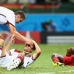 Germany's Thomas Muller, left on ground, and Ghana's John Boye feel the effects of their collision late in Saturday's 2-2 draw.