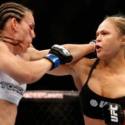 UFC women's bantamweight champion Ronda Rousey punches Alexis Davis in their UFC women's bantamweight championship fight at UFC 175.