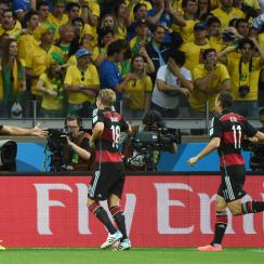 Germany's Sami Khedira, left, celebrates his side's fifth goal as stunned spectators look on during an astonishing 5-0 Brazil deficit in the opening 30 minutes of the World Cup semifinal.