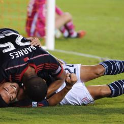 Darrius Barnes smothers Lee Nguyen after his go-ahead goal in the New England Revolution's 2-1 win over the Houston Dynamo.