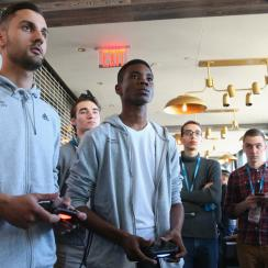 Demetri Anastasiou, left, competes in the FIFA Interactive World Cup. SI's Stanley Kay, third from right, watches on intently, scouting his future opponent