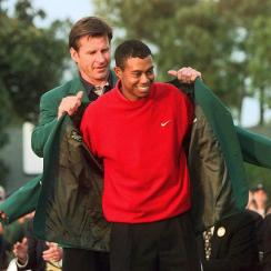 Tiger Woods receives the Masters green jacket for winning the 1997 Masters Tournament from 1996 winner Nick Faldo.